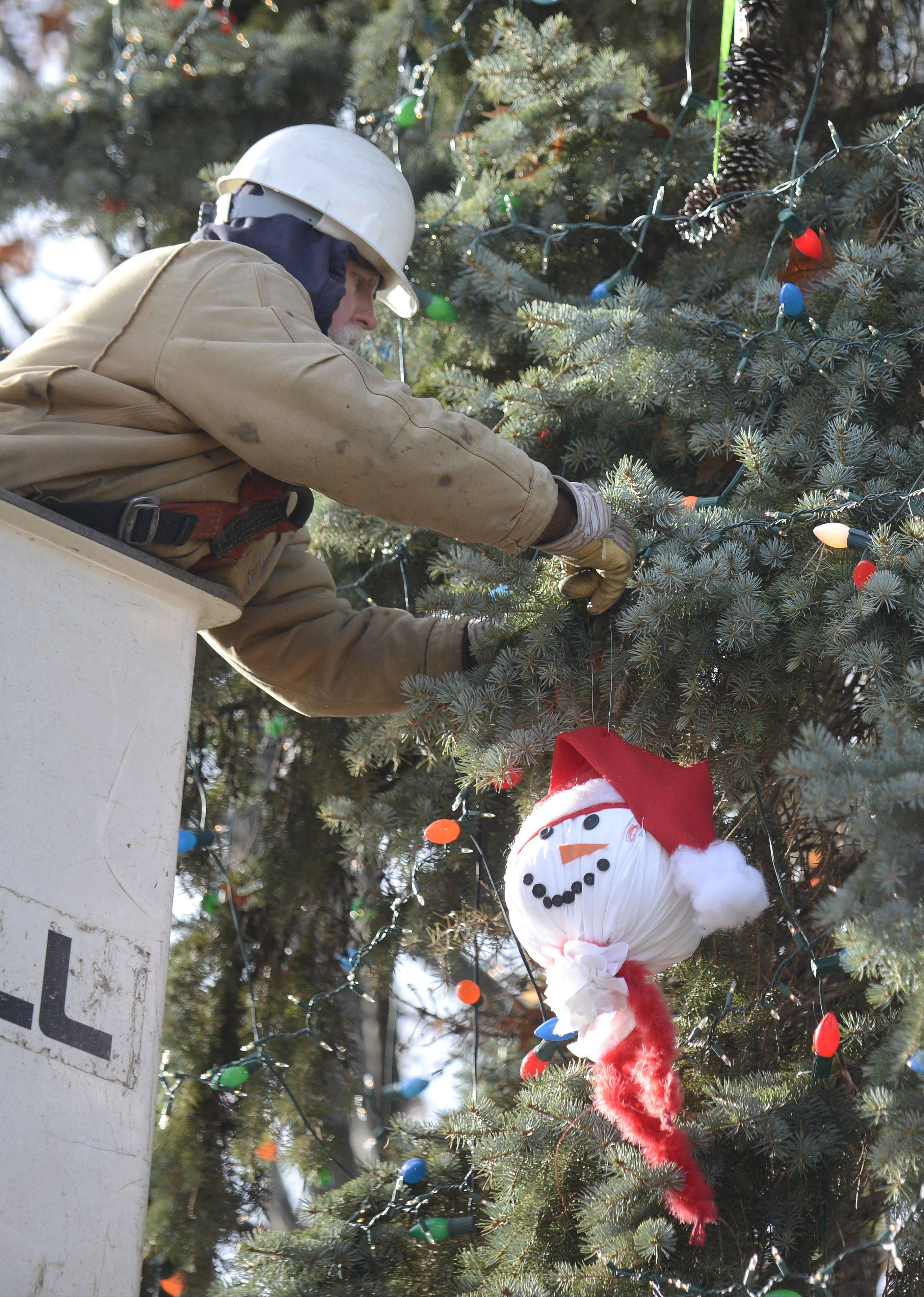 Geneva electric department lineman Keith Benson hangs ornaments made by local children Thursday on the city�s Christmas tree in front of the old courthouse on Third Street. The tree was decorated in preparation for the annual Christmas Walk and House tour festivities Friday and Saturday.