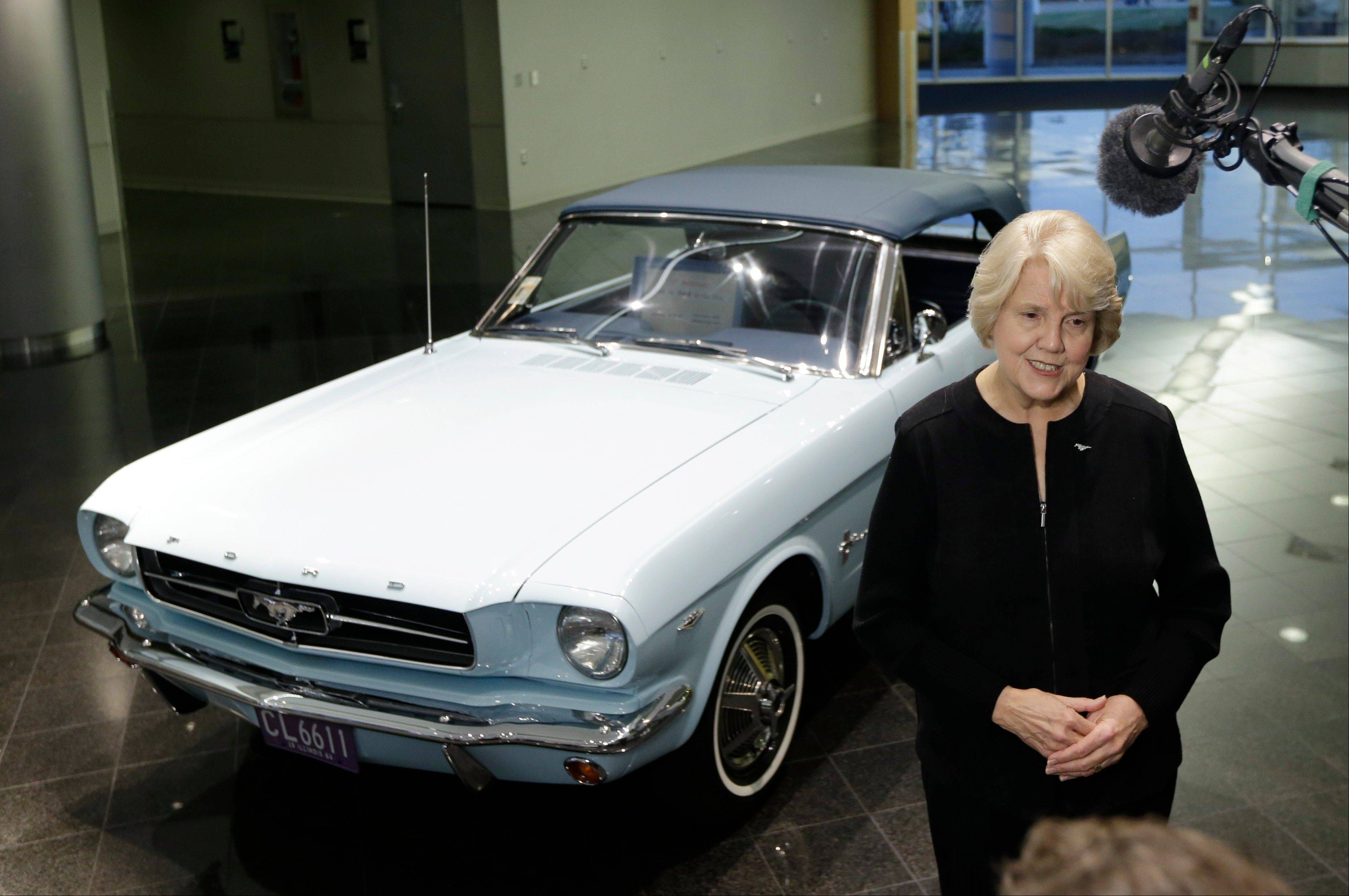 Gail Wise, of Park Ridge, owner of the first Mustang sold by Ford, background, is interviewed at the unveiling of the automaker�s new 2015 Ford Mustang in Dearborn, Mich., Thursday. Wise bought her car on April 15, 1964, two days before the official sales launch from a Ford dealership in Chicago.