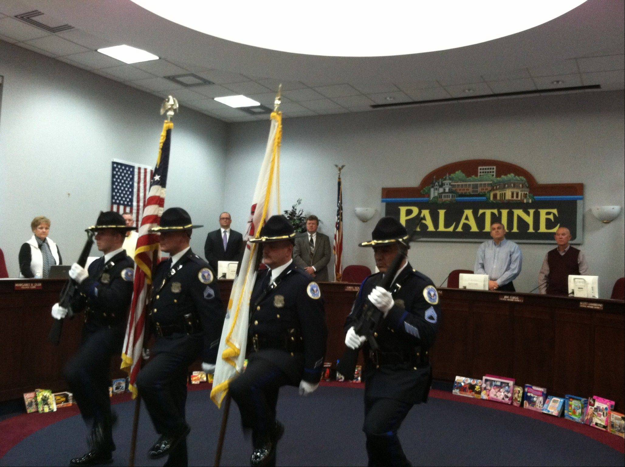 The Palatine police color guard leads the Pledge of Allegiance in honor of Pat and Mac McCoy, who were recognized by village leaders this week for their founding of the Yellow Ribbon Support Group. During its 10 years, the organization sent more than 28,000 care packages to troops serving overseas.