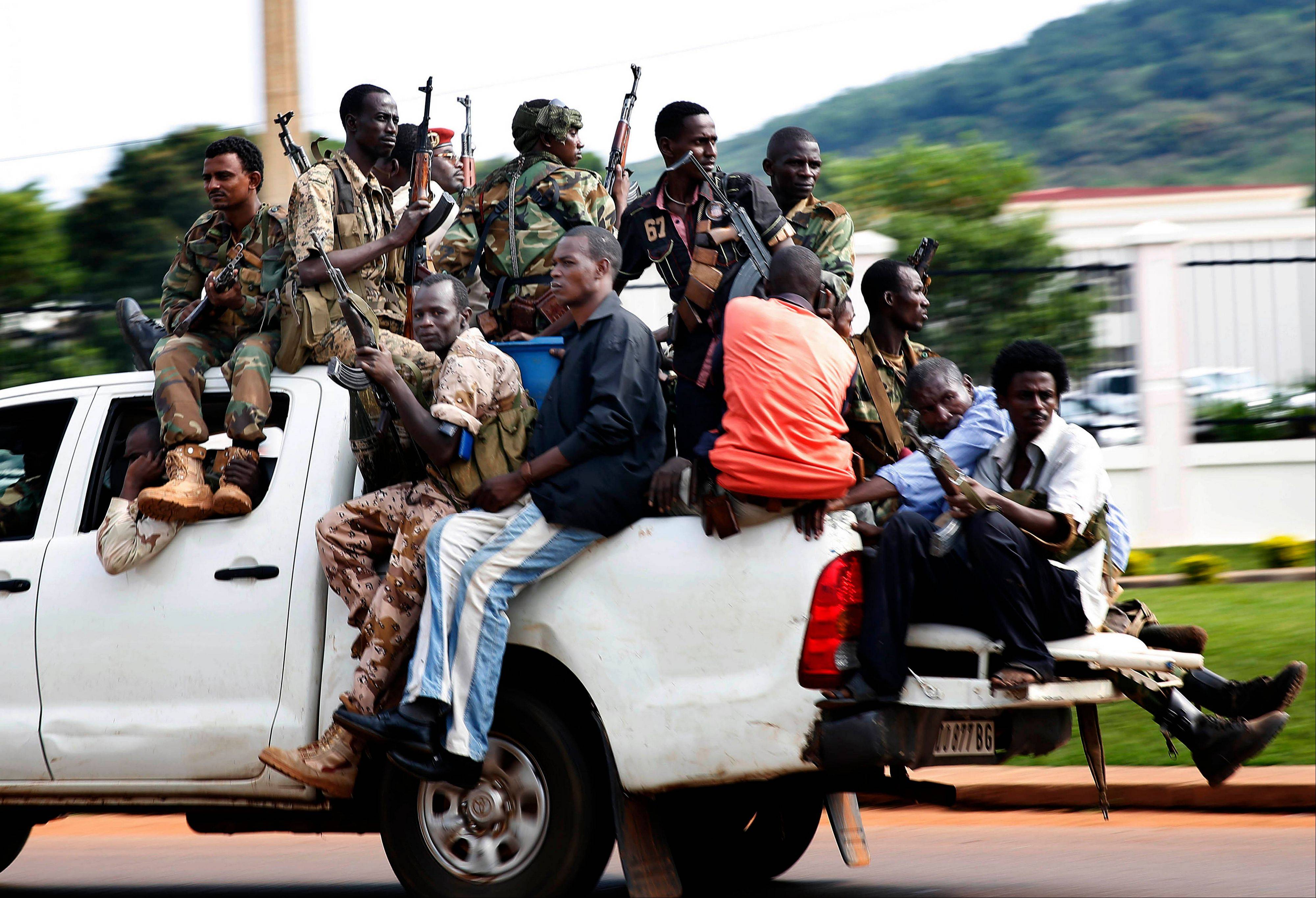 Seleka soldiers race through Bangui, Central African Republic, Thursday, as gunfire and mortar rounds erupt in the town.