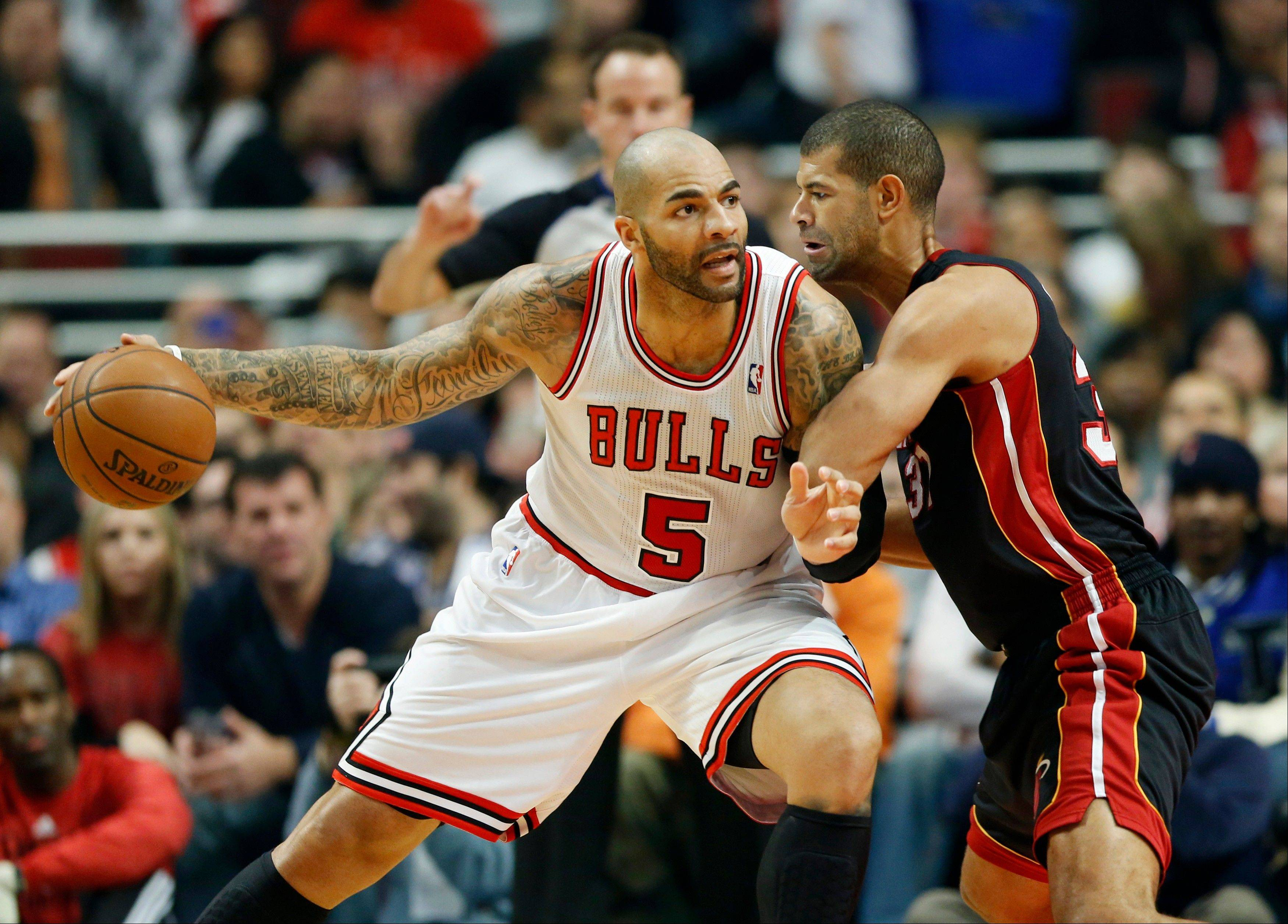 Associated Press Bulls forward Carlos Boozer, left, looks for an opening against Miami Heat forward Shane Battier, right, during the first half of an NBA basketball game at the United Center Thursday.