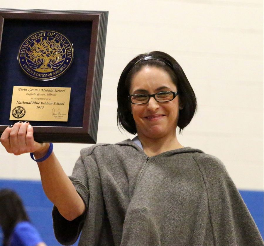 Jessica Barnes, principal of Twin Groves Middle School in Buffalo Grove, holds up the school's Blue Ribbon School award during a celebration program Thursday. Twin Groves was one of three Northwest suburban schools to earn the prestigious honor this year.