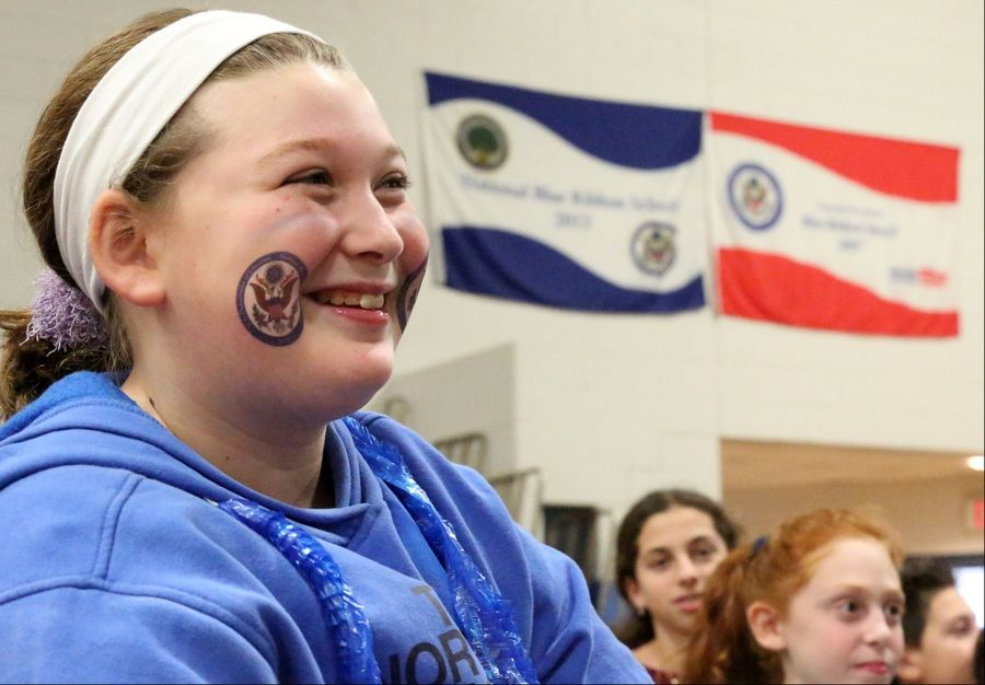 With two blue ribbon banners behind her, Twin Groves Middle School sixth-grader Hannah Getlin is all smiles Thursday during a program celebrating the Blue Ribbon School award received from the U.S. Dept. of Education. The school won the award this year and in 2007. Only four middle schools in Illinois received the award this year, according to Principal Jessica Barnes.