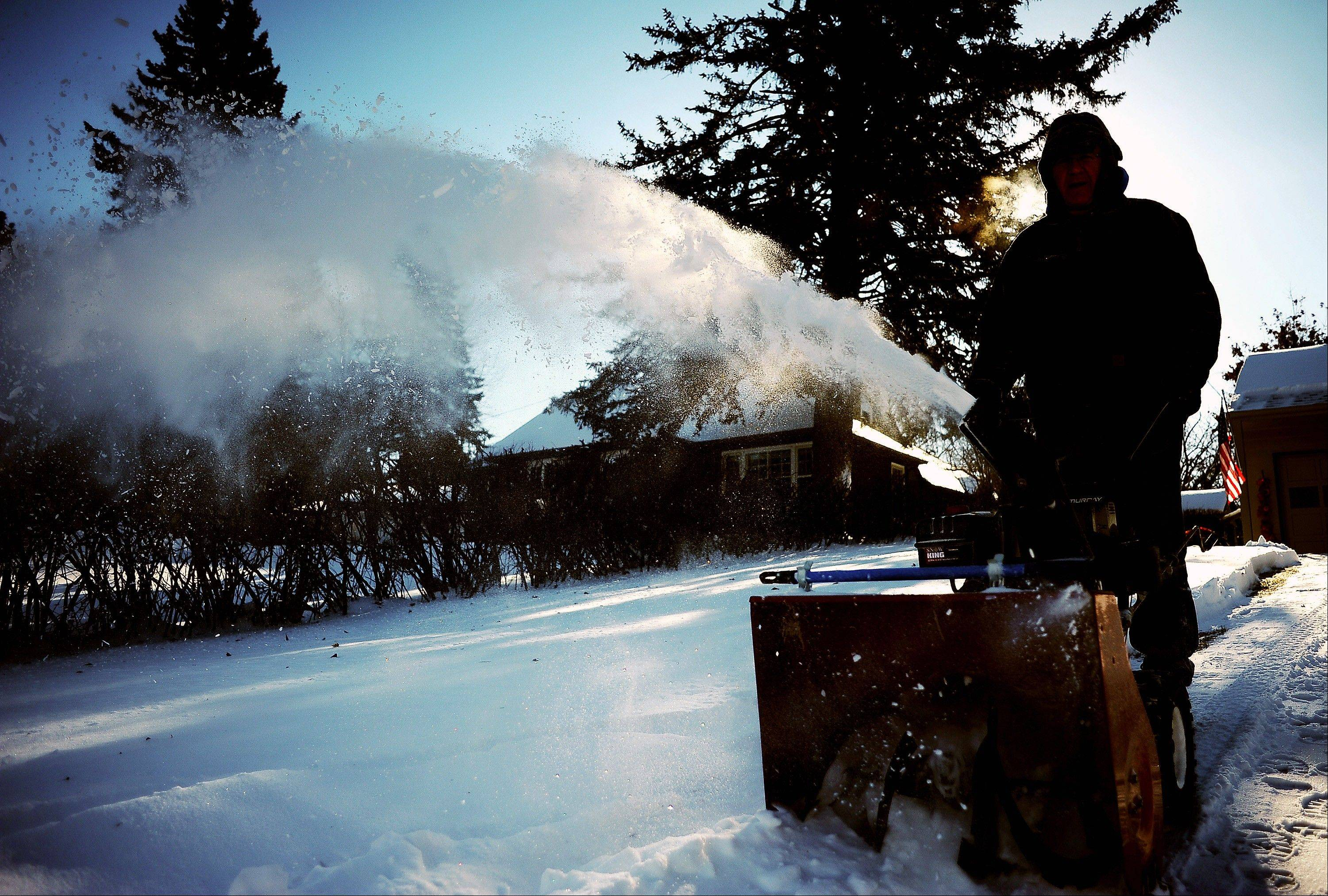 Bill Earley cleans off his driveway in Sioux Falls, S.D., on Thursday, Dec. 5, 2013.