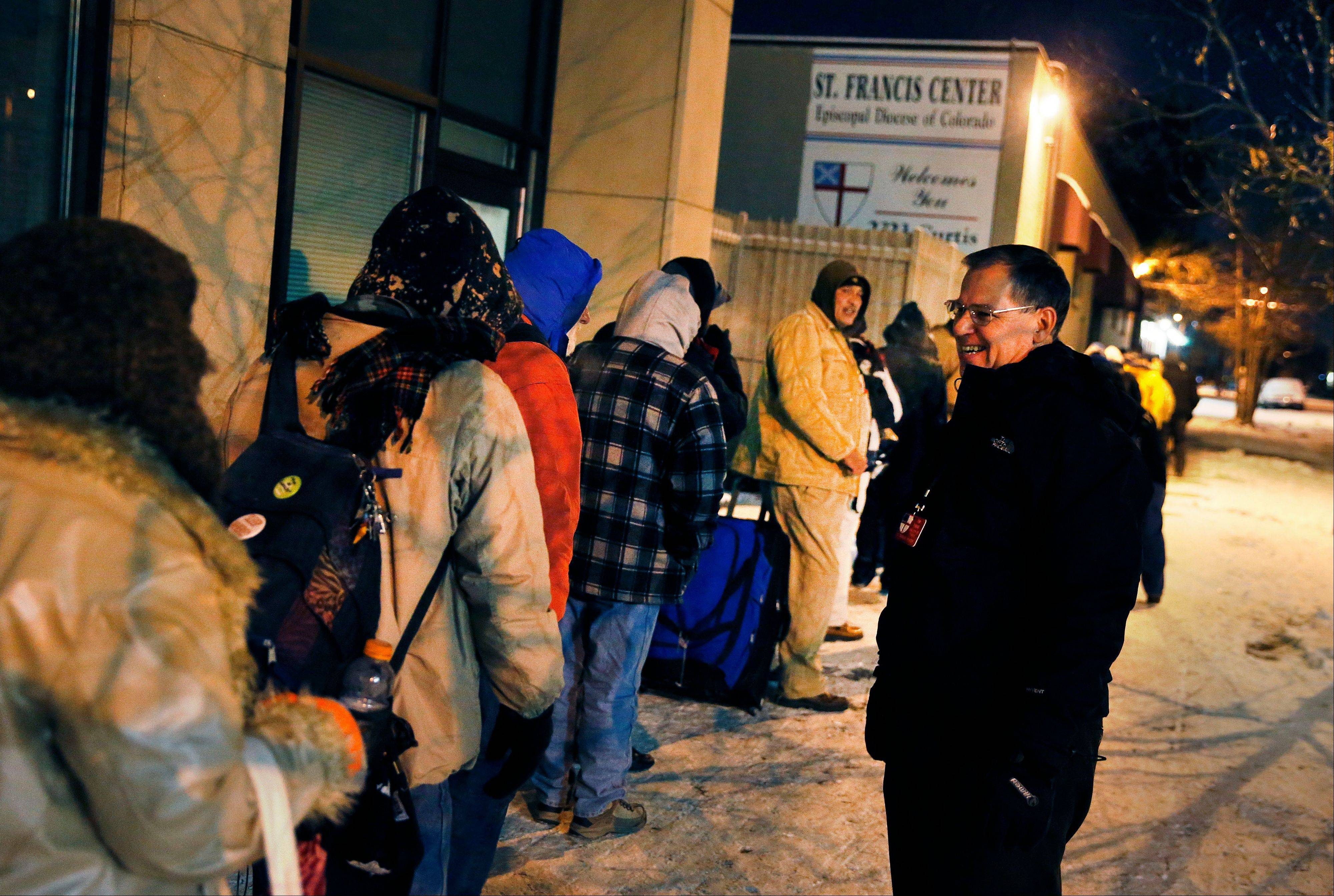 Before dawn and in -9 degree weather, Tom Tuning, right, greets men who wait for the opening of the St. Francis Center's day shelter, where Tuning is finance director, in downtown Denver, Thursday Dec. 5, 2013.