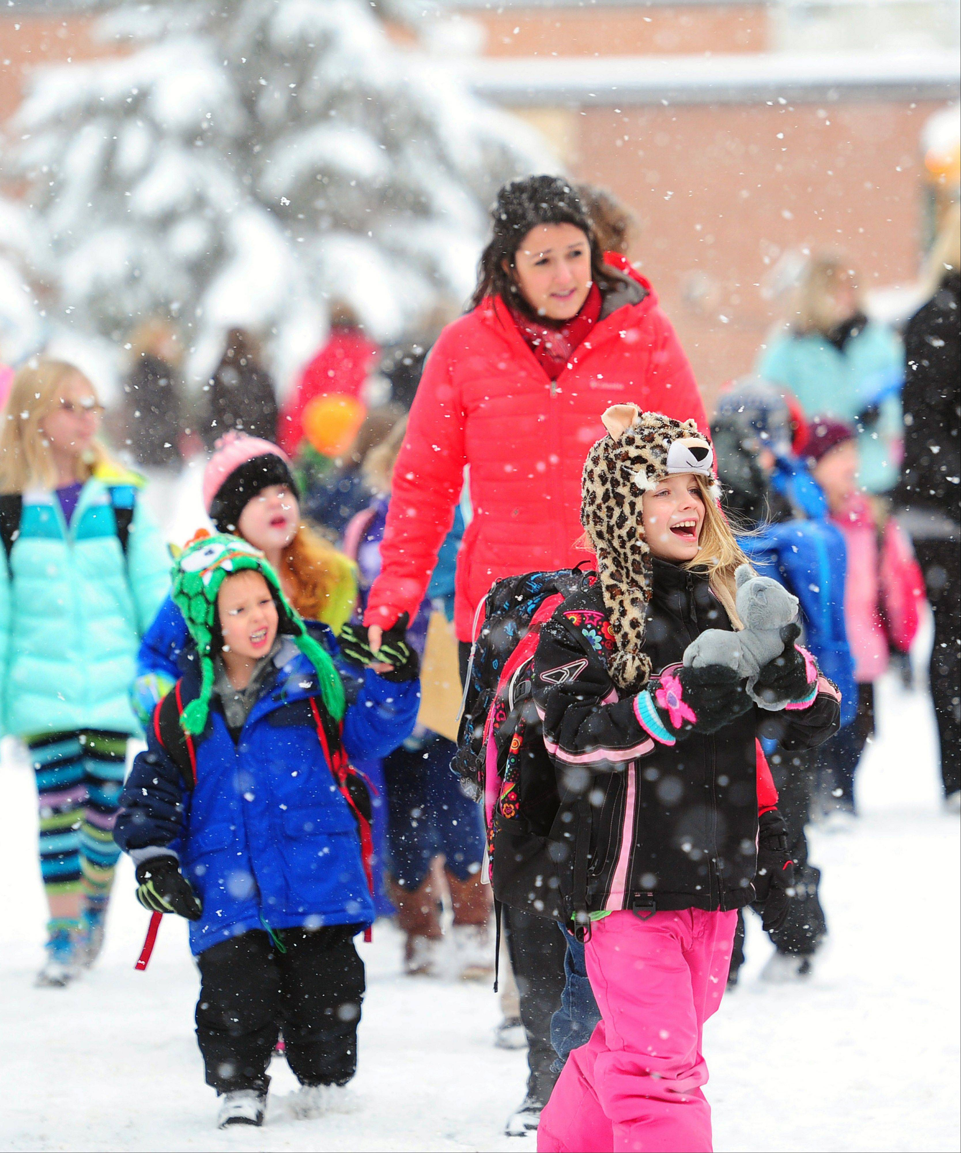 Riverside Elementary students and teachers walk to the waiting school buses on Wednesday Dec. 4, 2013, in Brainerd, Minn. Schools were open as the storm reached into the second day in Central Minnesota.
