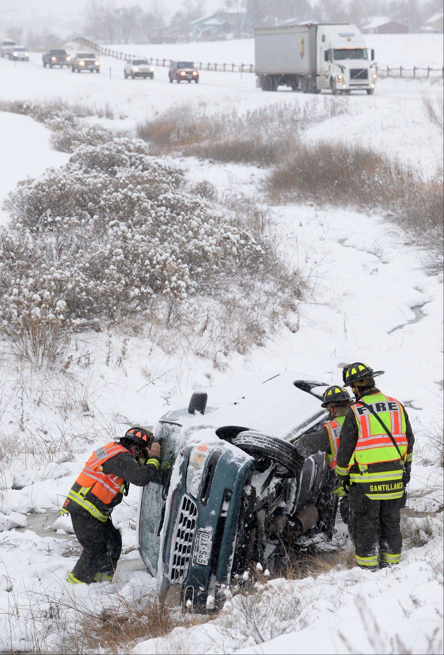 Poudre Fire Authority fire fighters check for survivors in a van that had rolled into a ditch along Carpenter Road south of Fort Collins, Colo., Wednesday Dec. 4, 2013.
