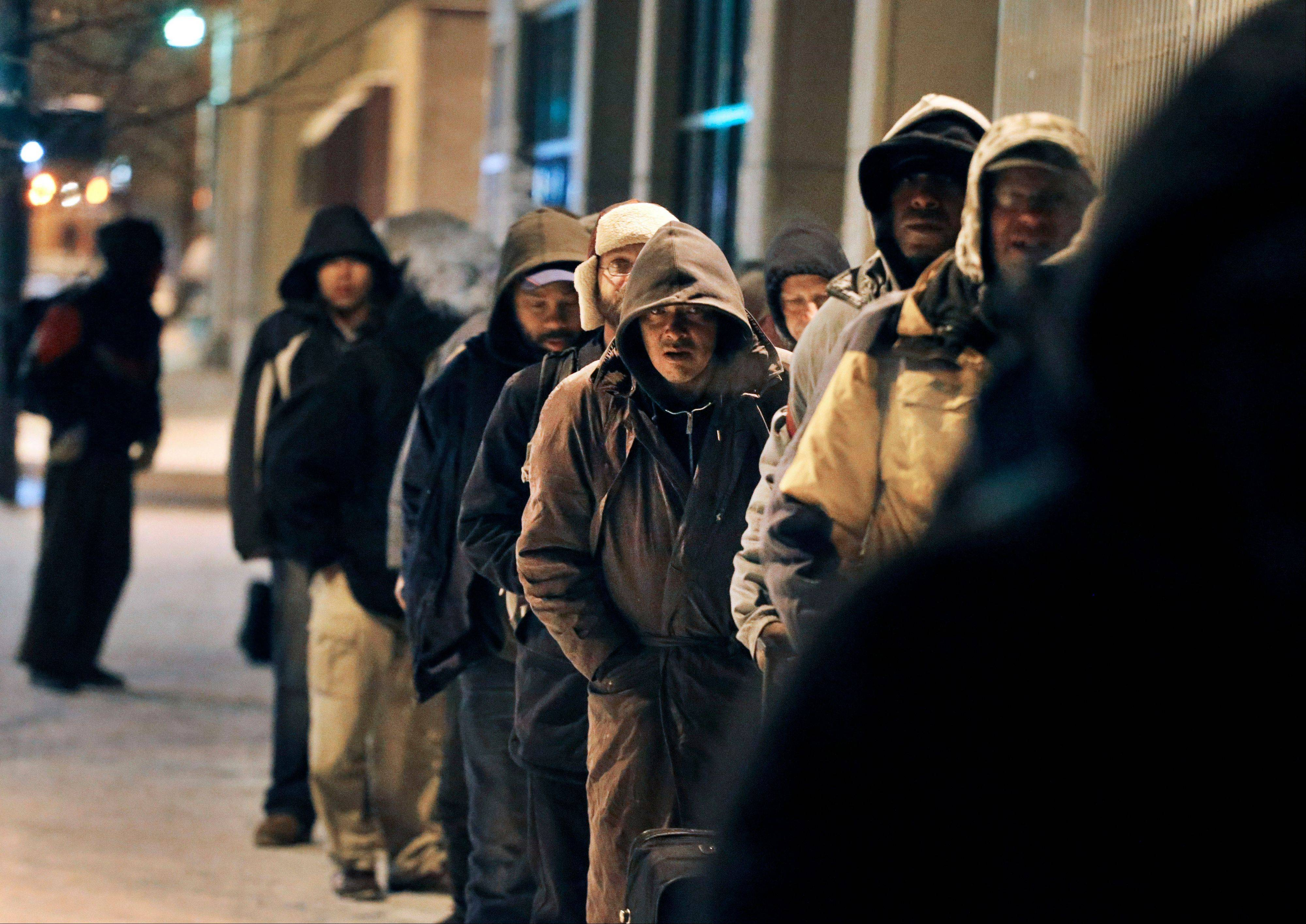 Before dawn and in -9 degree weather, men wait for the opening of the St. Francis Center's day shelter, in downtown Denver, Thursday Dec. 5, 2013.