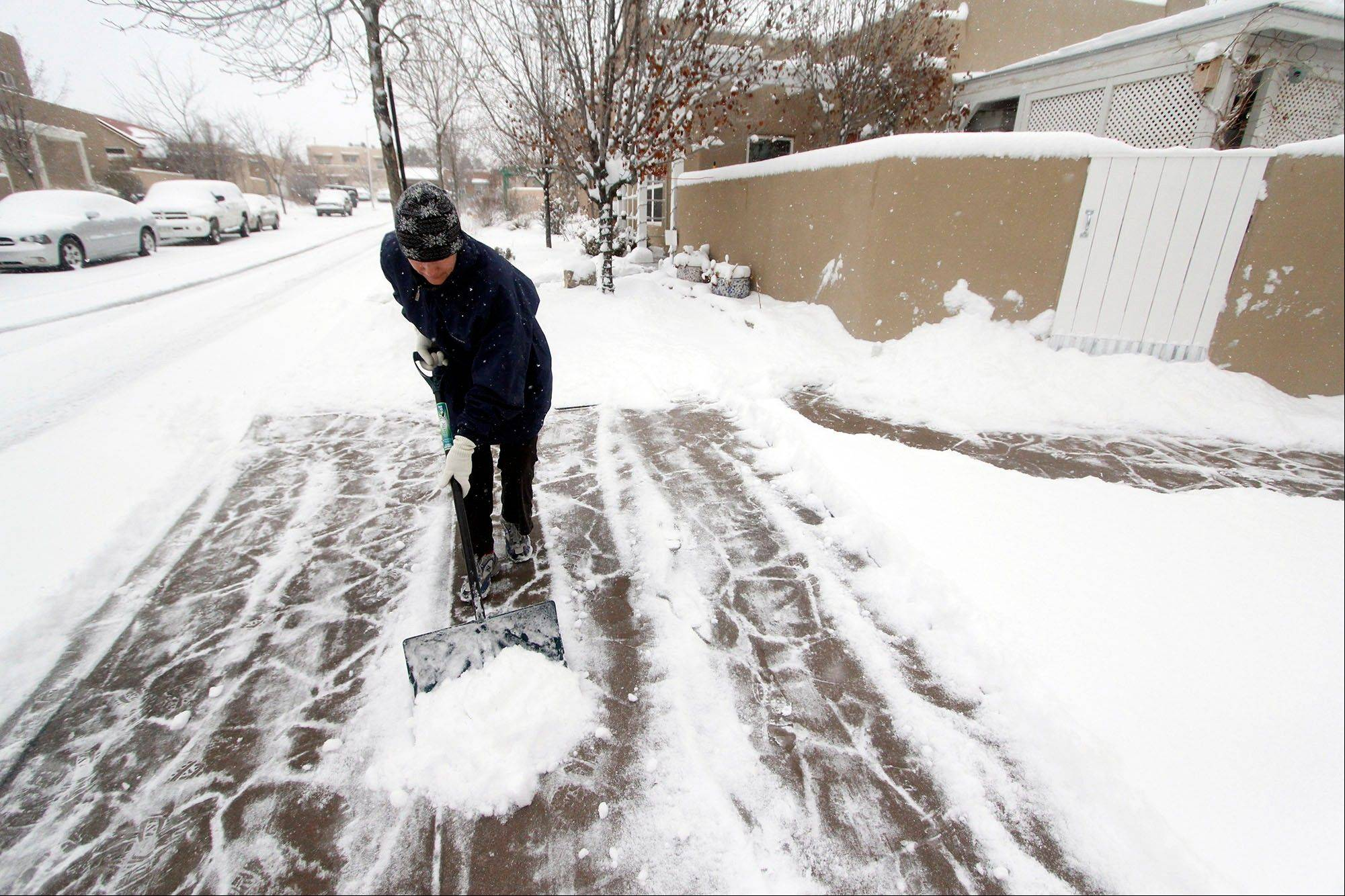 Colleen Martinez shovels snow off her driveway in Santa Fe, N.M., Tuesday, Dec, 5, 2013.