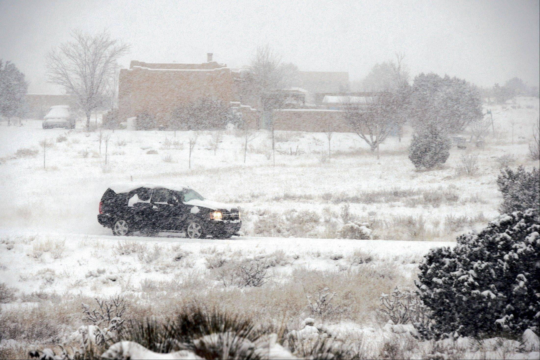 A driver makes their way up a snow covered Monte Alto Rd in Eldorado, N.M., early Thursday, Dec. 5, 2013. Some northern New Mexico highways have difficult driving conditions Thursday as the latest blast of freezing temperatures, wind and snow causes delays and closures in parts of the state.