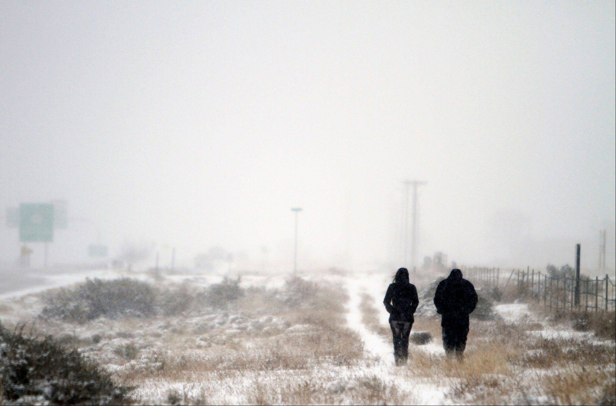 Jennifer Maez, left, and Jared Romero go out for a stroll in the snow on the Frontage Road along I-25 near Santa Fe, N.M. Thursday, Dec. 5, 2013.