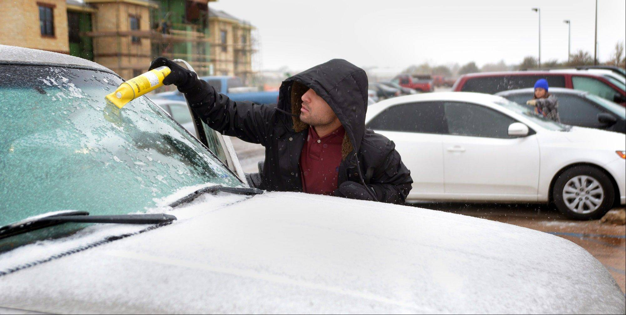 George Lara, a graduate student at the University of Texas, uses a deicer to clear the windshield of his car on Thursday, Dec. 5, 2013, in Odessa, Texas.