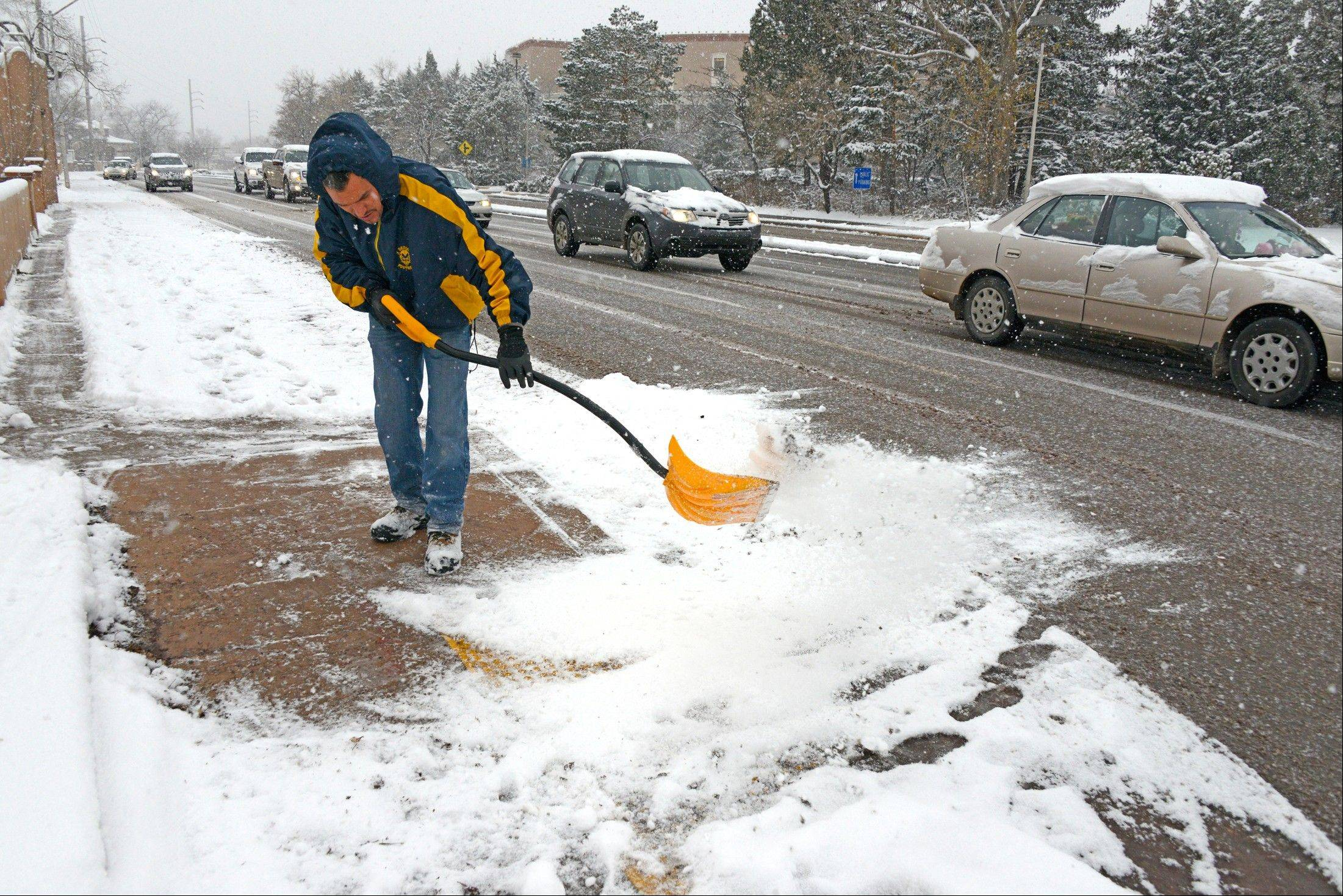 David Palomino clears the sidewalk of snow on Thursday, Dec. 5, 2013 in Santa Fe, N.M.