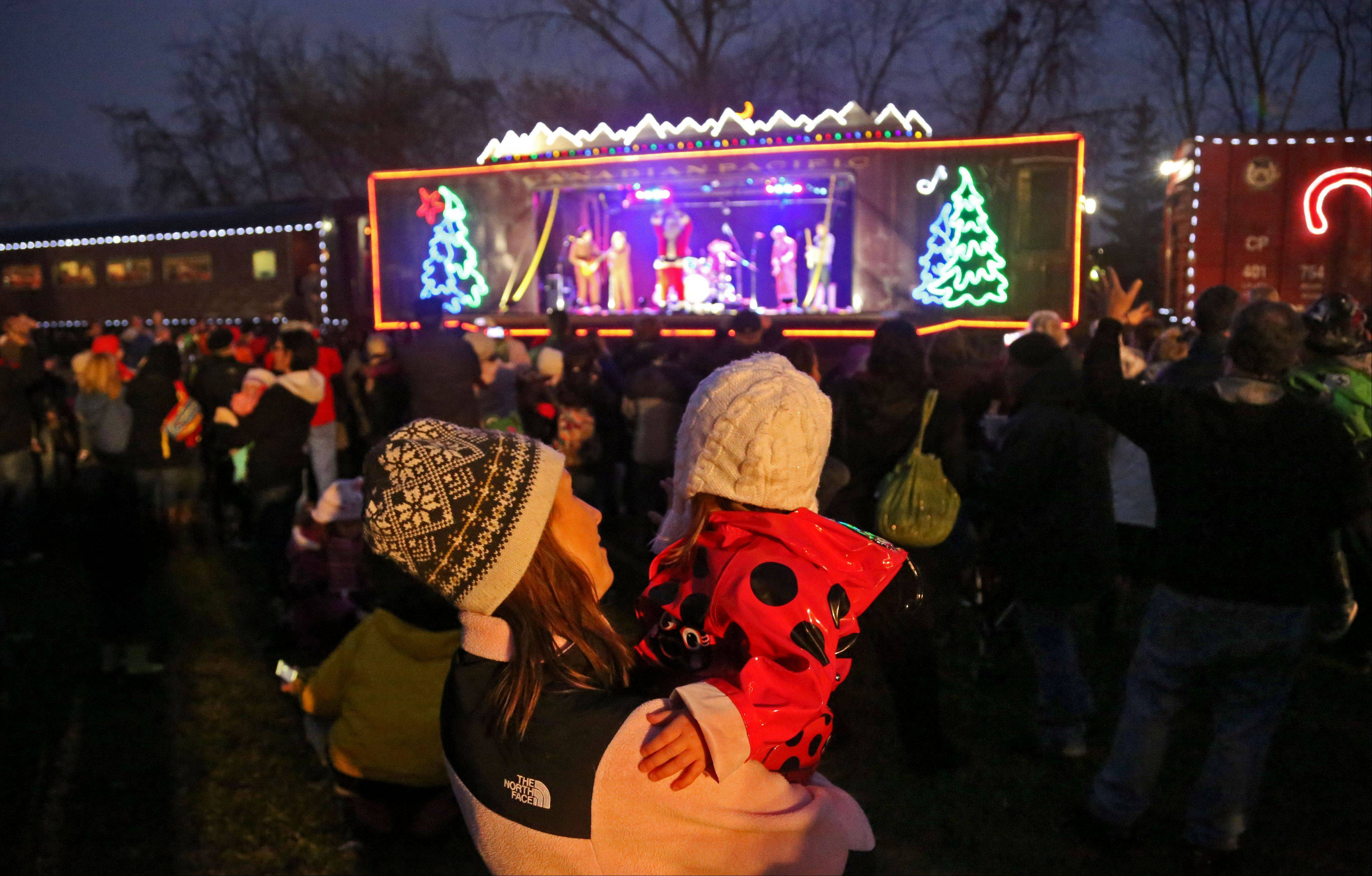 People listen to music by the Claytones as the 15th annual Canadian Pacific Holiday Train stops on Depot Road in Gurnee Wednesday. Food and funds were collected to benefit the Northern Illinois Food Bank.