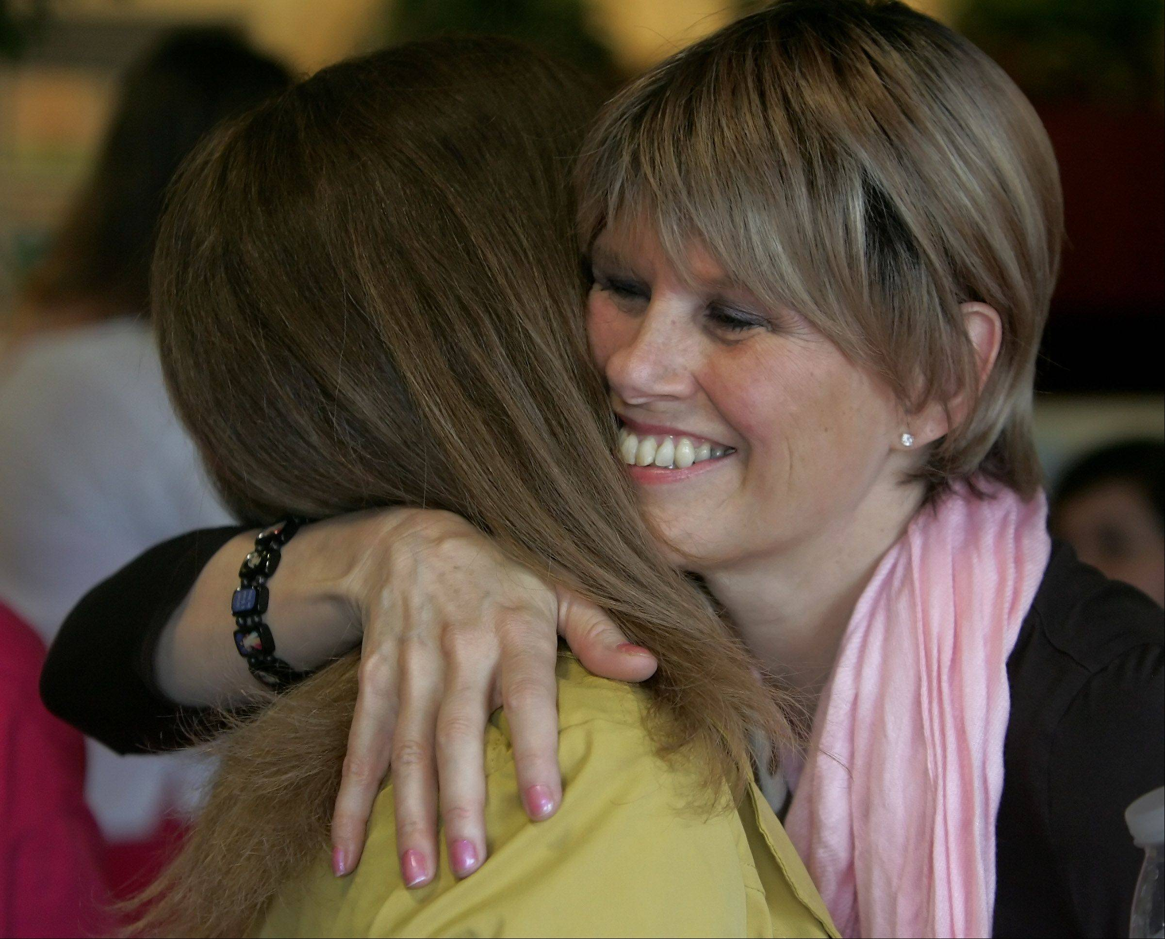 Mount Prospect teacher Linda Frahm receives a hug from a friend in 2012. Frahm is fighting cancer, and her colleagues at Lions Park Elementary School have organized a fundraiser for her that will include an appearance by writer-actress Bonnie Hunt.