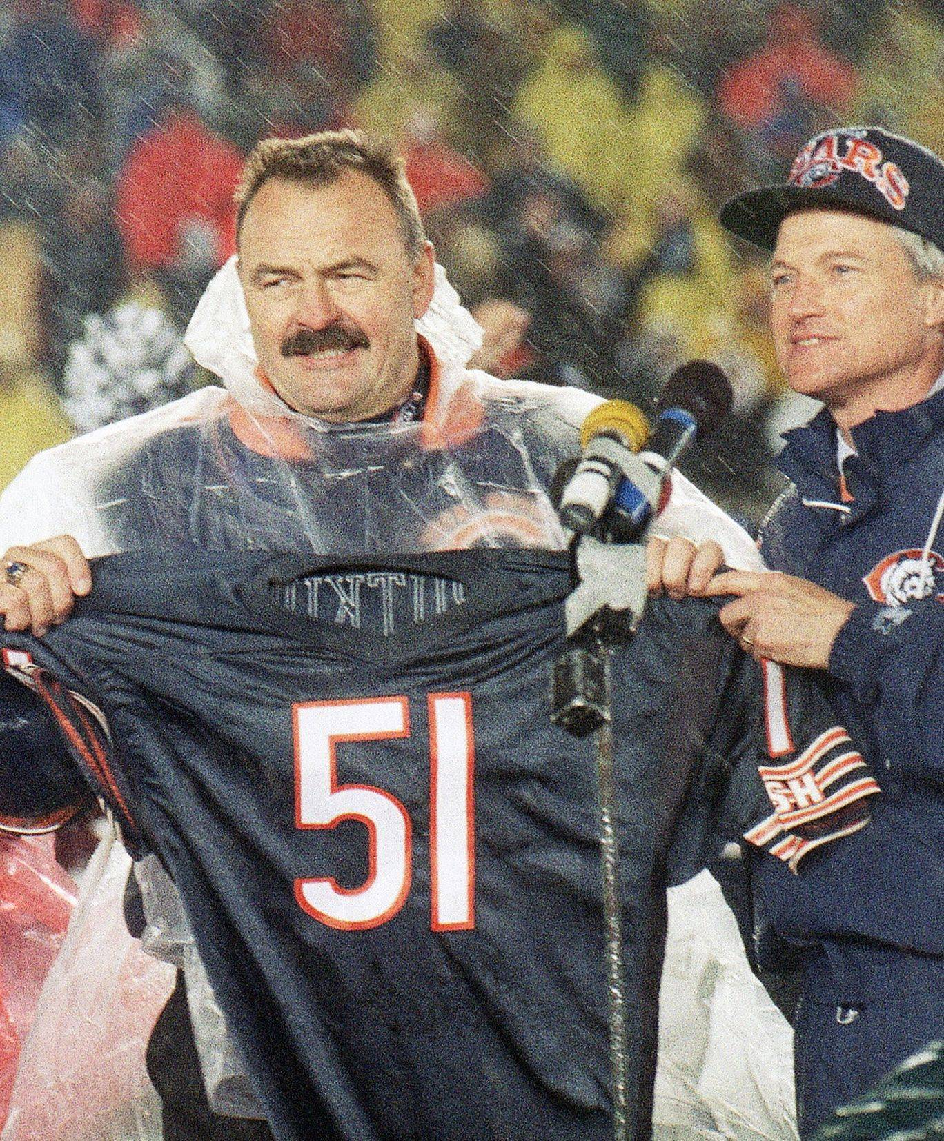 Dick Butkus (left) and Gale Sayers holds up their jerseys during a driving rainstorm on Oct. 31, 1994, when the Bears retired both Hall of Famers numbers.