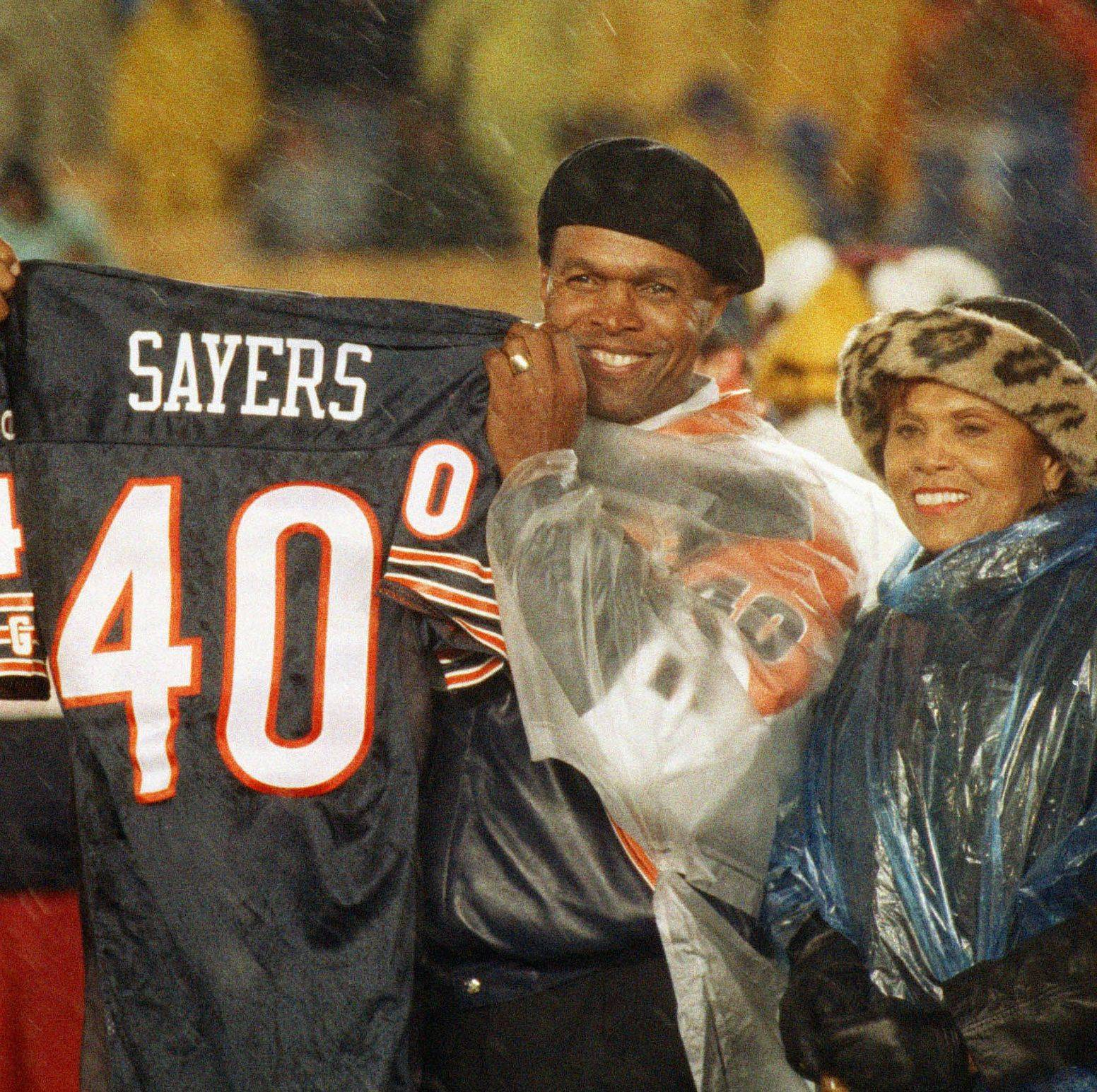 Gayle Sayers holds a jersey during halftime ceremoniese in the Bears' game with the Green Bay Packers at Soldier Field in Chicago Oct. 31, 1994. The Bears retired the uniform numbers of Sayers and linebacker Dick Butkus.