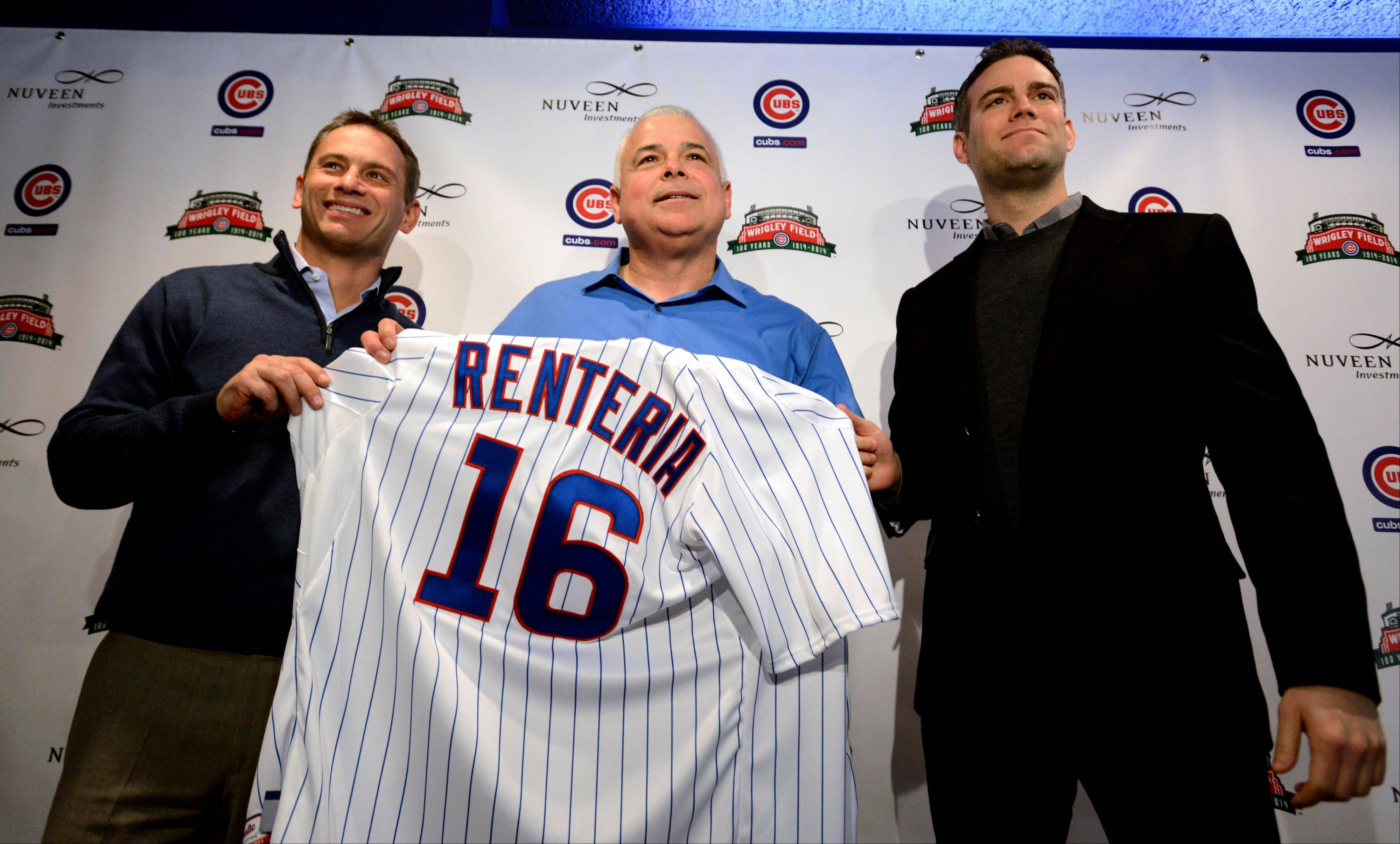 Cubs new manager Rick Renteria, center, receives a jersey from Chicago Cubs President of Baseball Operations Theo Epstein, right, and Chicago Cubs Vice President and General Manager Jed Hoyer during a press conference at Wrigley Field in Chicago, Thursday, Dec., 5, 2013. Renteria met with the media for the first time since he was hired last month while recuperating in San Diego from hip surgery.