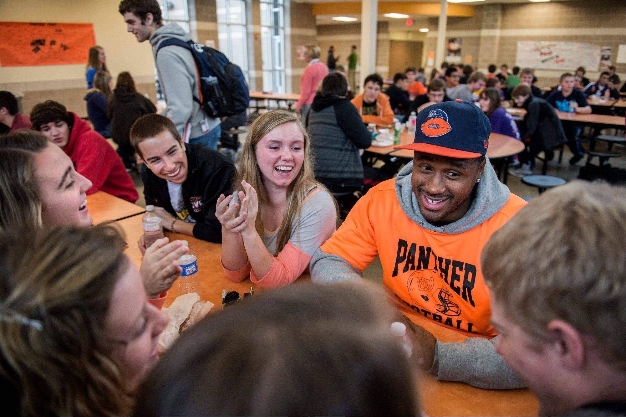 Bears linebacker James Anderson, second from left lightens the mood for Washington High School students as he sits with them during lunch Wednesday.