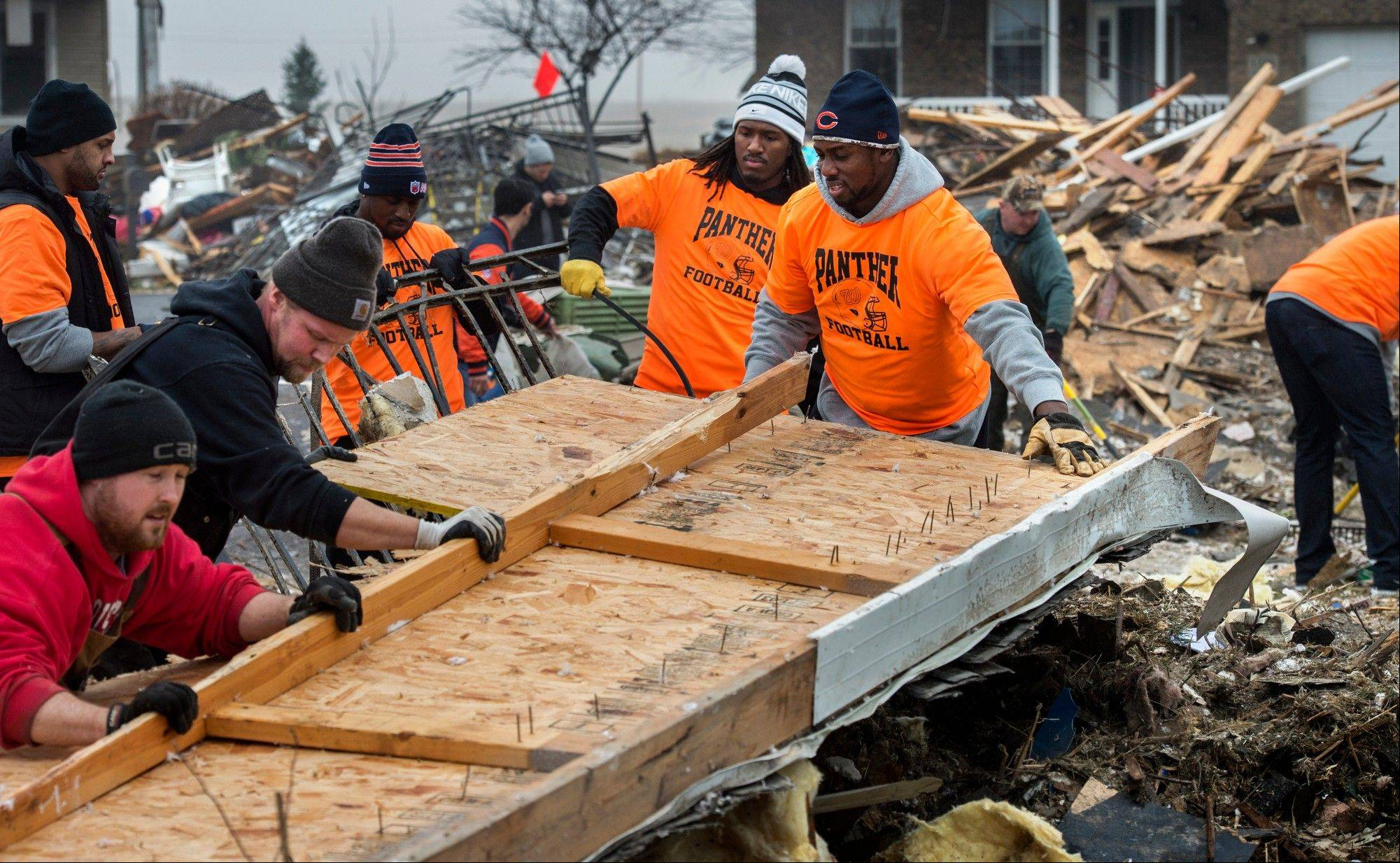 Defensive end Cheta Ozougwu, center right, along with other members of the Bears clear debris Wednesday along Dorchester Court in Washington, Ill.