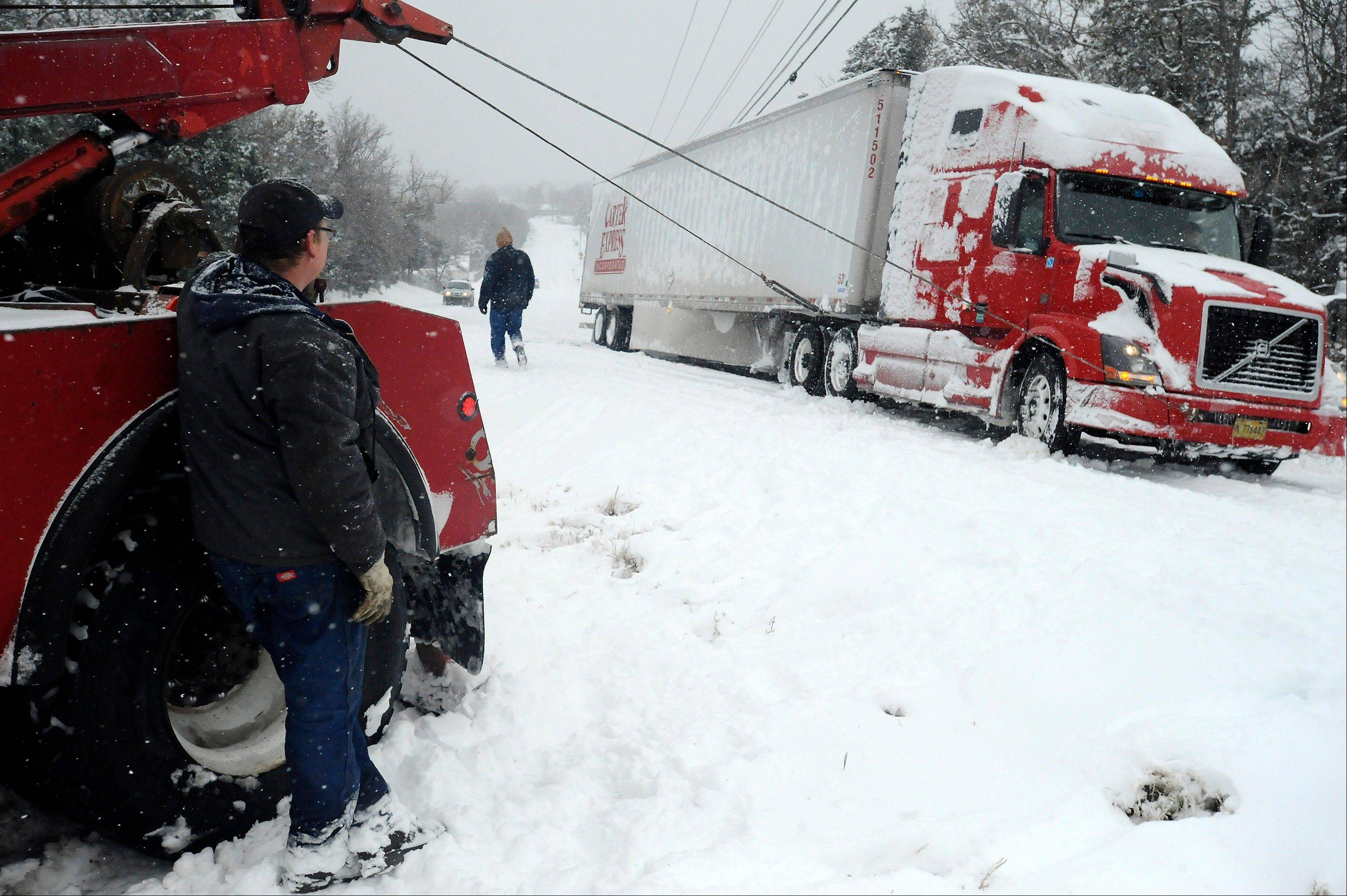 Jim Dobbs, left, helps pull a tractor trailer rig out of a ditch Friday in Henderson, Ark.