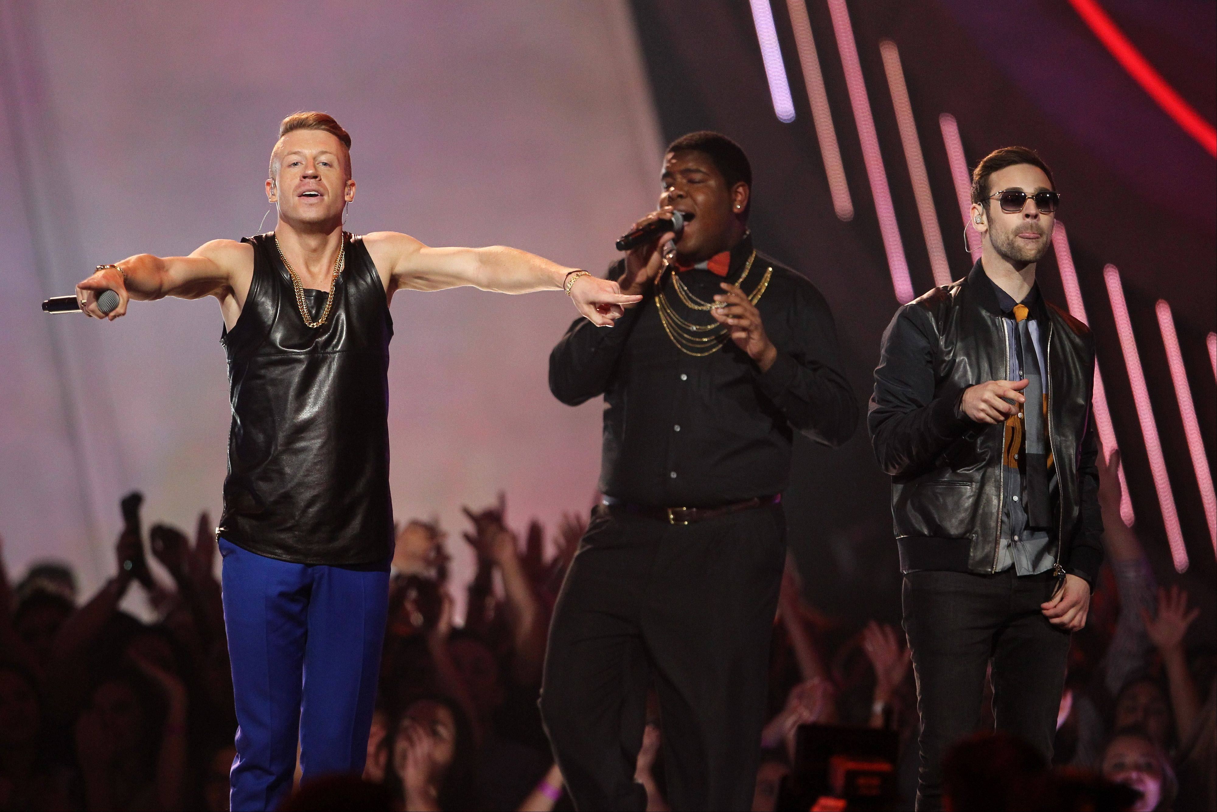 "Macklemore, left, and Ryan Lewis perform ""Can't Hold Us"" with Ray Dalton at the MTV Movie Awards in Sony Pictures Studio Lot in Culver City, Calif. Macklemore and Ryan Lewis are among the clear favorites as The Recording Academy prepares to unveil its Grammy nominees on Friday."