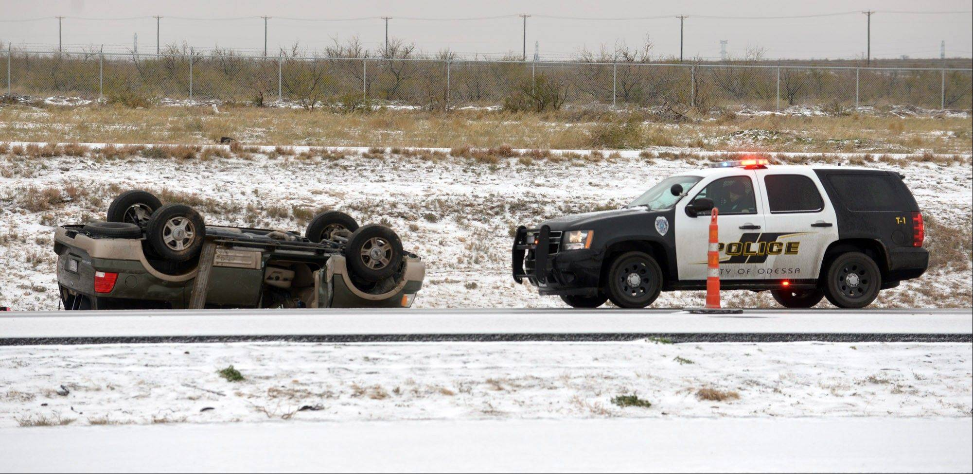 Police respond to a rolled over vehicle that crashed on the slick eastbound lanes of Interstate 20 near Odessa, Texas, Friday morning.