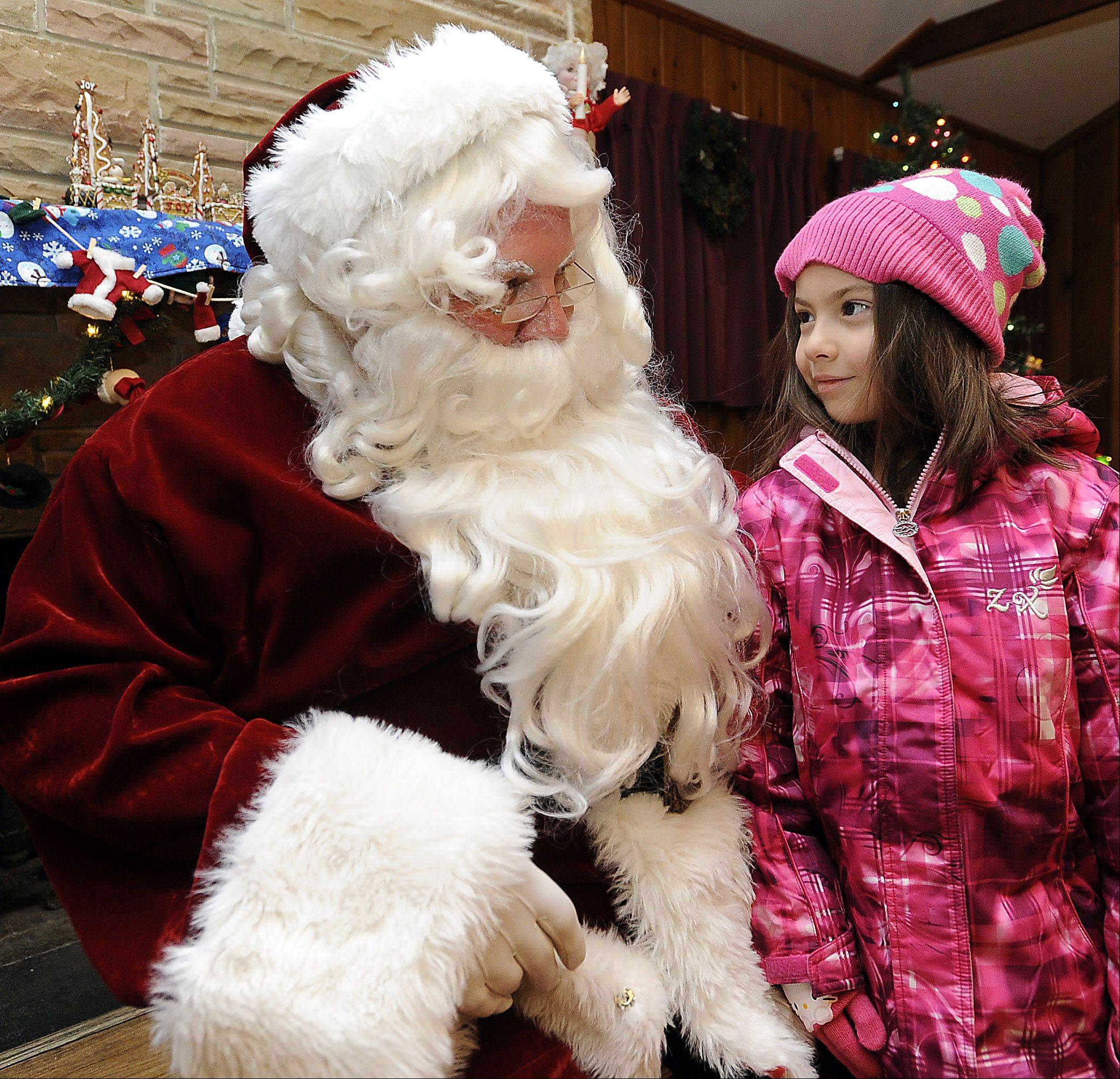 Santa talks to Isabella Kaspari, 6, of Bartlett at the tree-lighting ceremony on Friday.