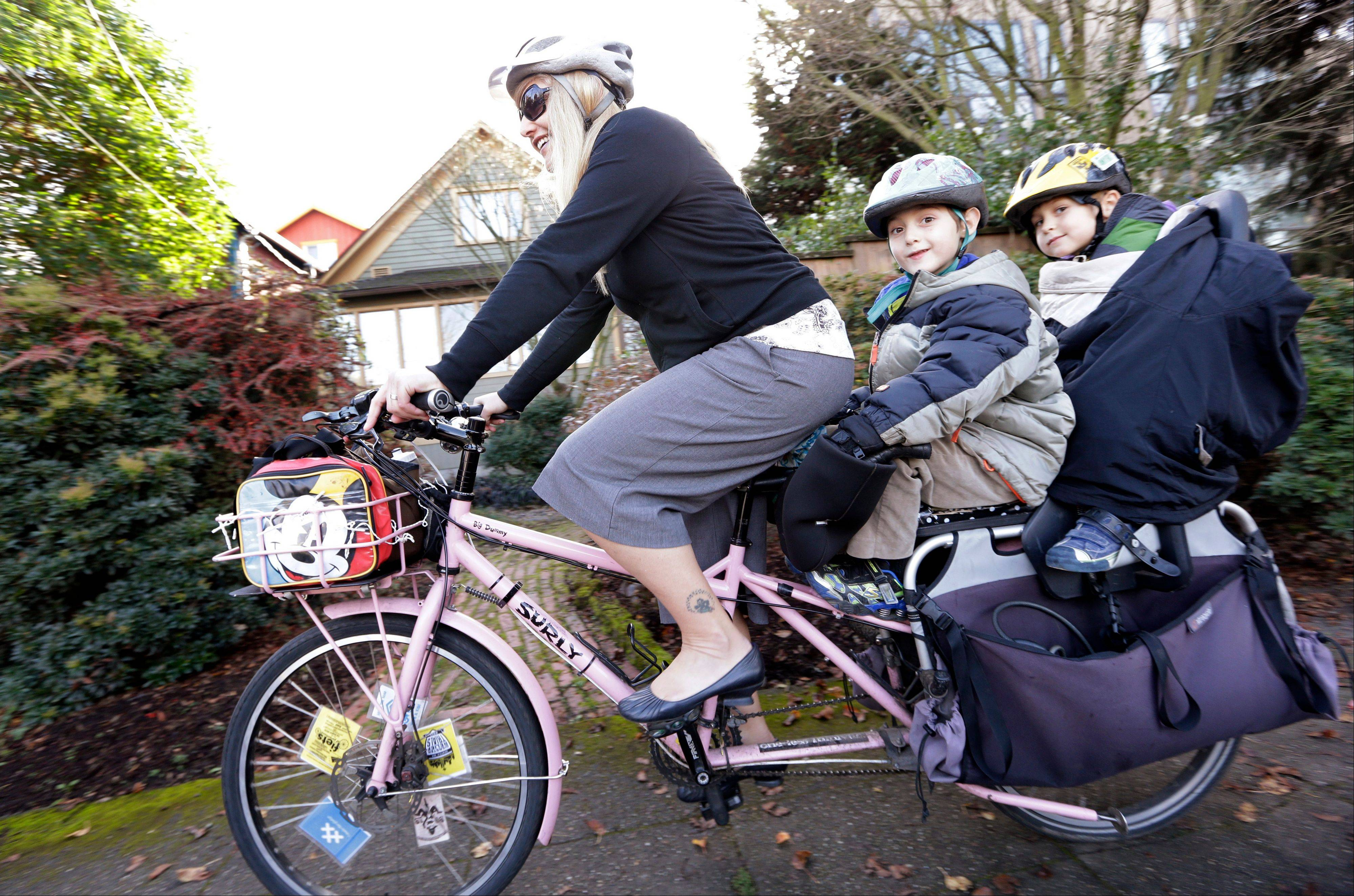 Madi Carlson pedals as her sons Rijder, 4, right, and Brandt, 6, ride aboard the family cargo bike as they head to an after-school gym program in Seattle.