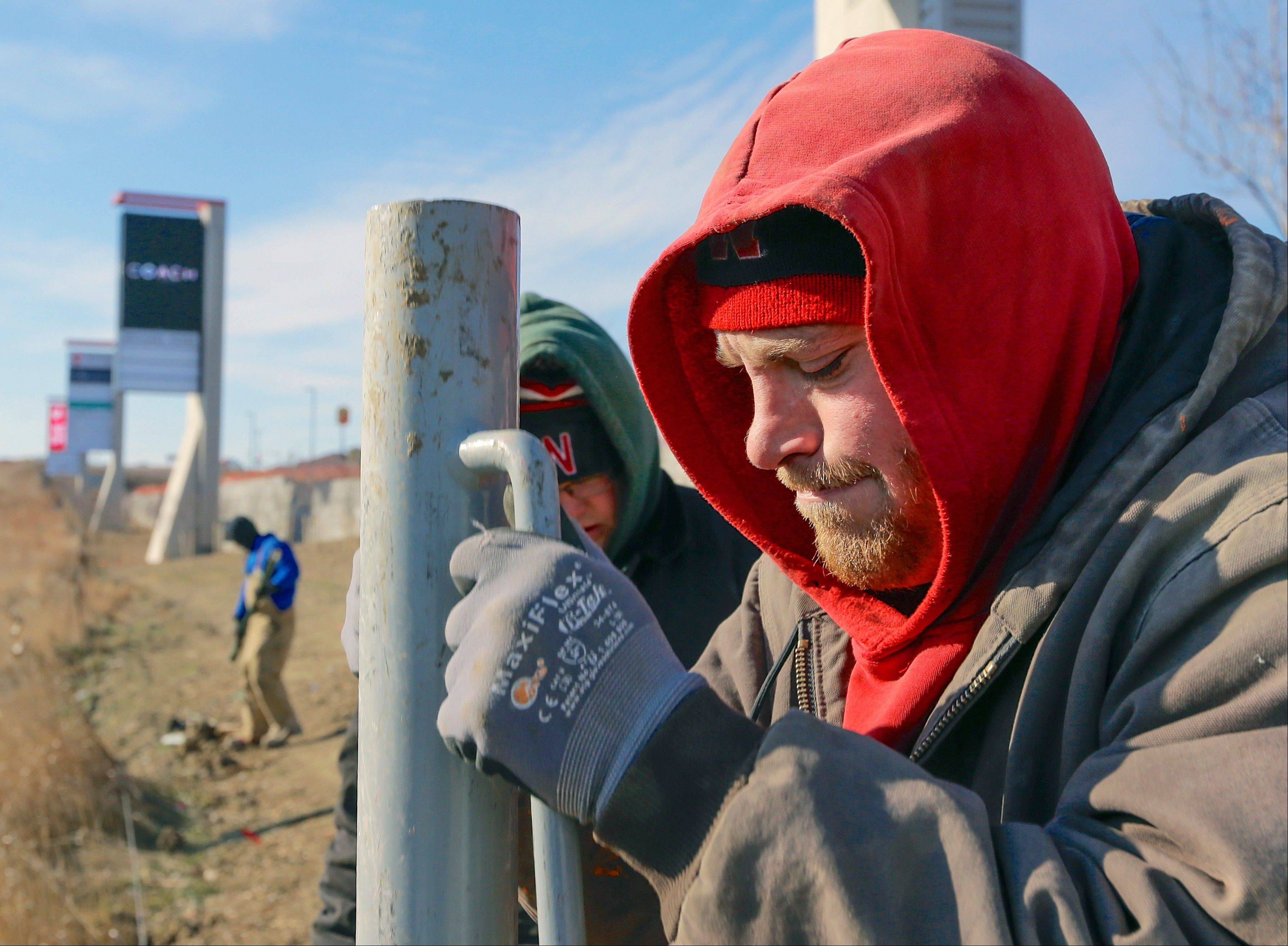 Craig Sheldon is all bundled up Friday as he plants fence posts into the ground in sub-freezing conditions, in Gretna, Neb.