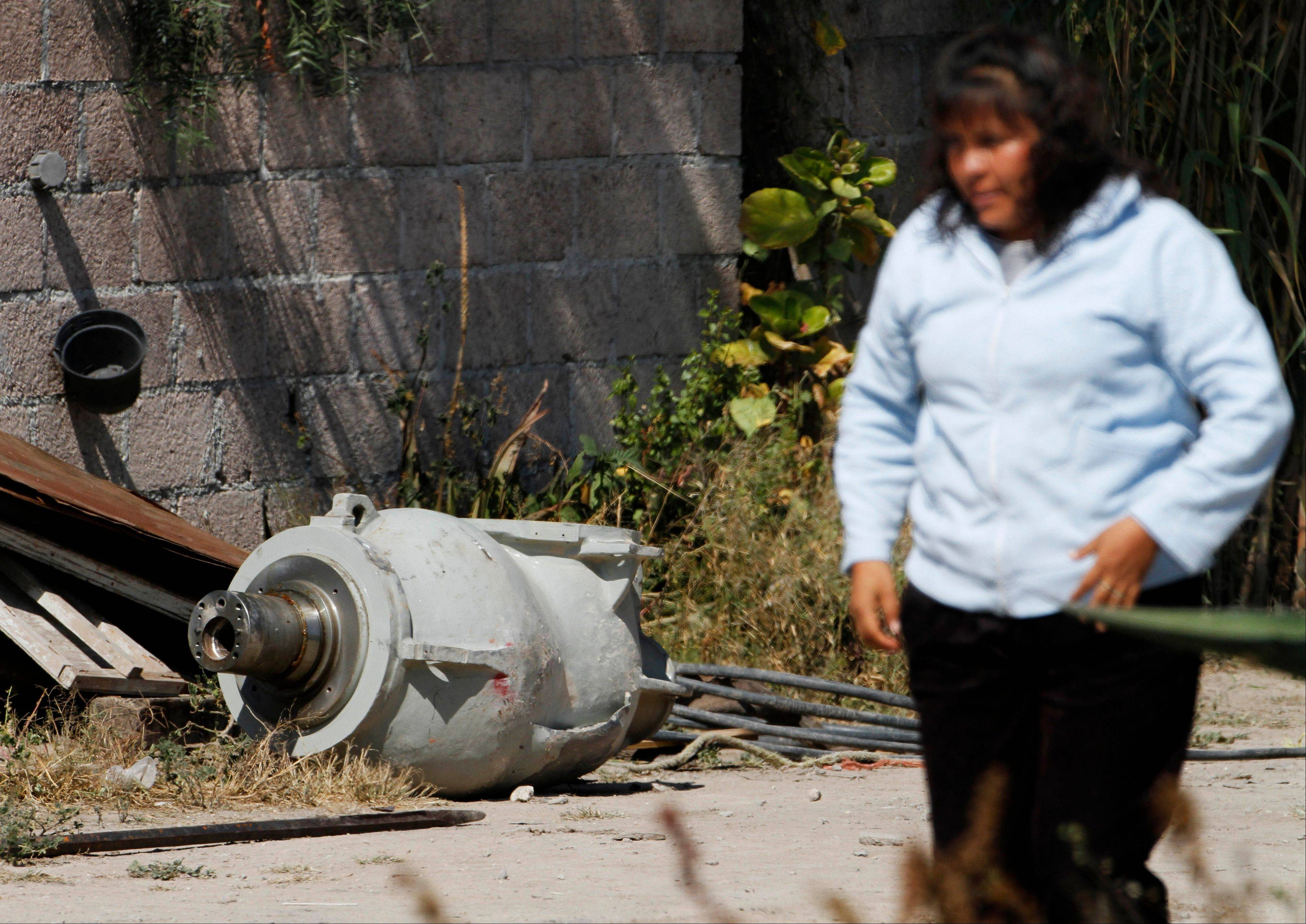 A woman walks Thursday near a radiation head that was part of a radiation therapy machine, in the patio of the family who found the abandoned equipment in a nearby field in the village of Hueypoxtla, Mexico.