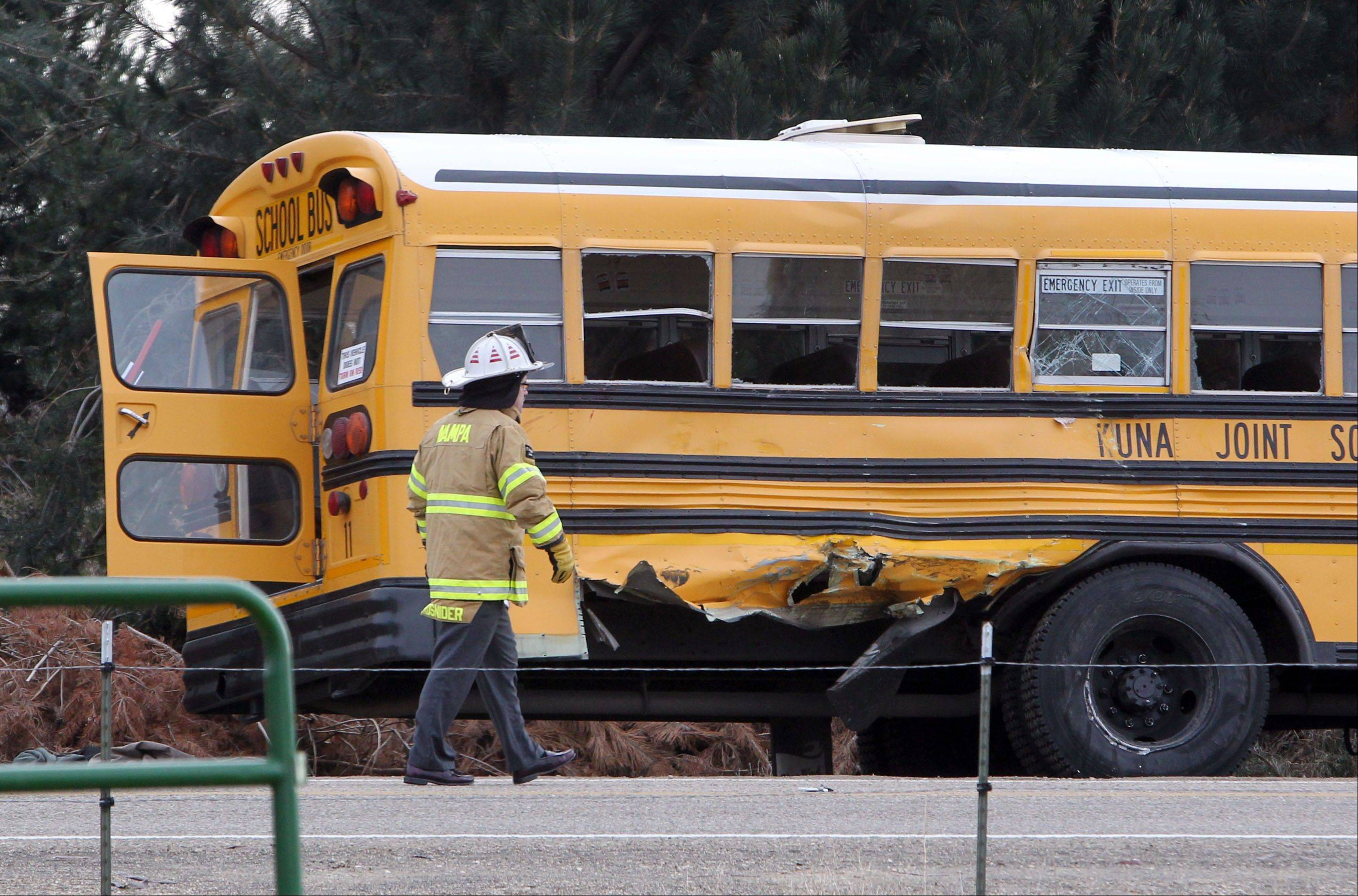 A firefighter walks past the damaged Kuna School District bus at the scene of a fatal crash on Thursday, Dec. 5, 2013 in Kuna, Idaho. Authorities say one child has died and five people were injured, including four children, when a dump truck collided with the school bus carrying elementary school students in Kuna, a town about 30 minutes from Boise.
