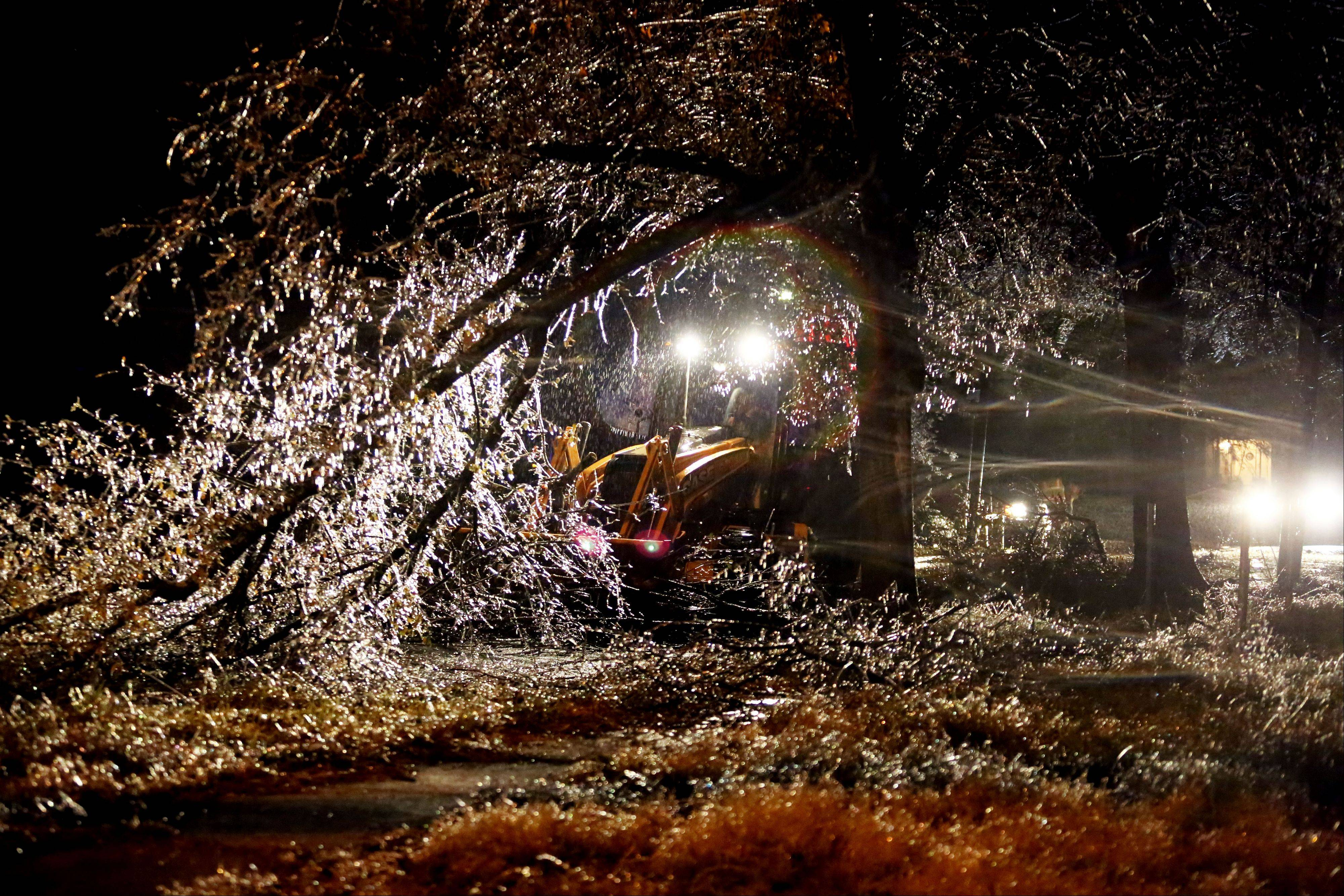 City of Paris Street Department employees use clear a large tree that fell blocking a road. A winter storm moved into North East Texas Friday, Dec. 6 2013 bringing with it freezing rain, ice and temperatures in the low 20�s.