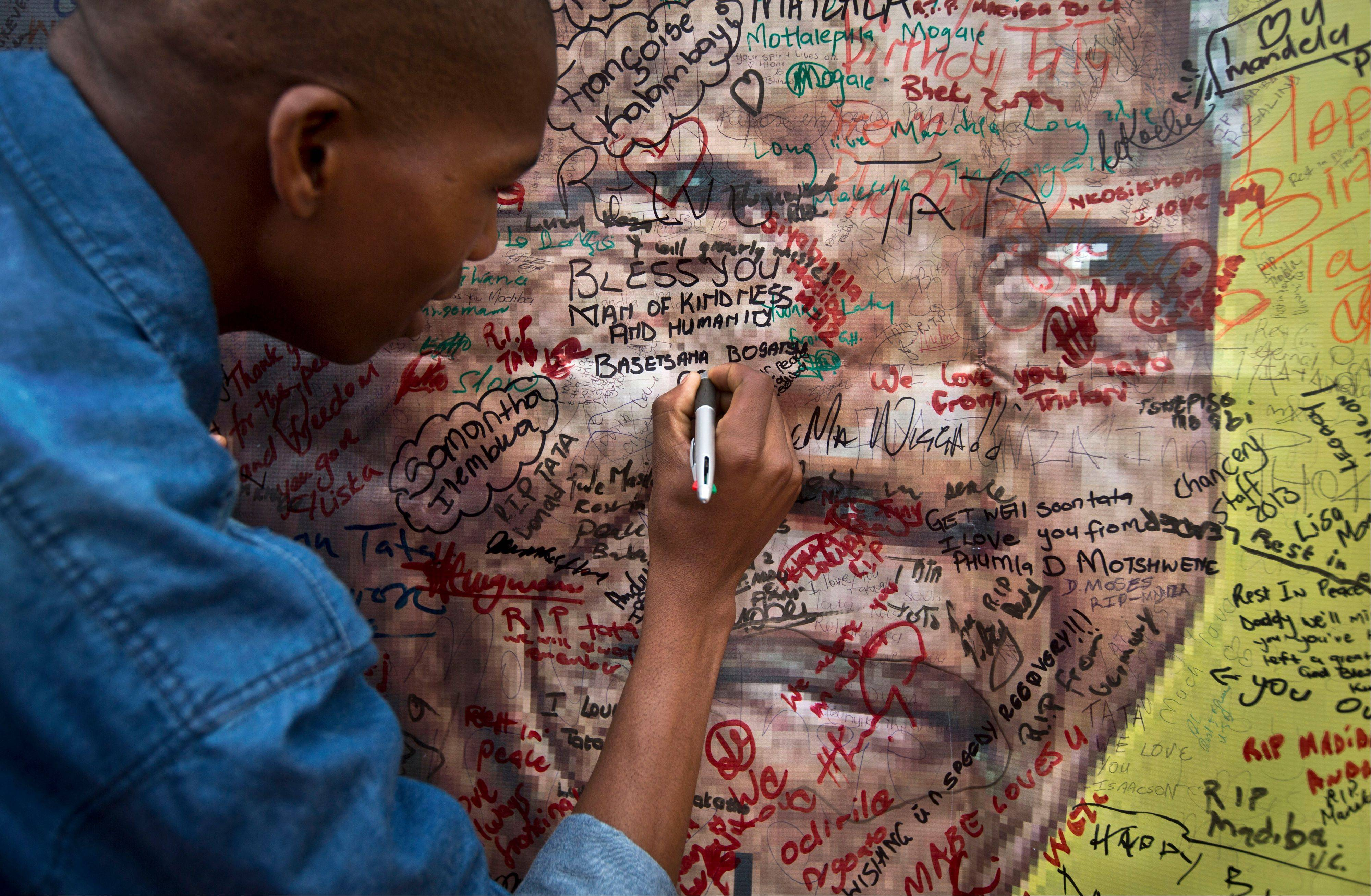 A well-wisher writes a message on a poster of Nelson Mandela, on which he and others have written their messages of condolence and support, in the street Friday outside his old house in Soweto, Johannesburg. Flags were lowered to half-staff and people in black townships, in upscale mostly white suburbs and in South Africa�s vast rural grasslands commemorated Nelson Mandela with song, tears and prayers on Friday while pledging to adhere to the values of unity and democracy that he embodied.