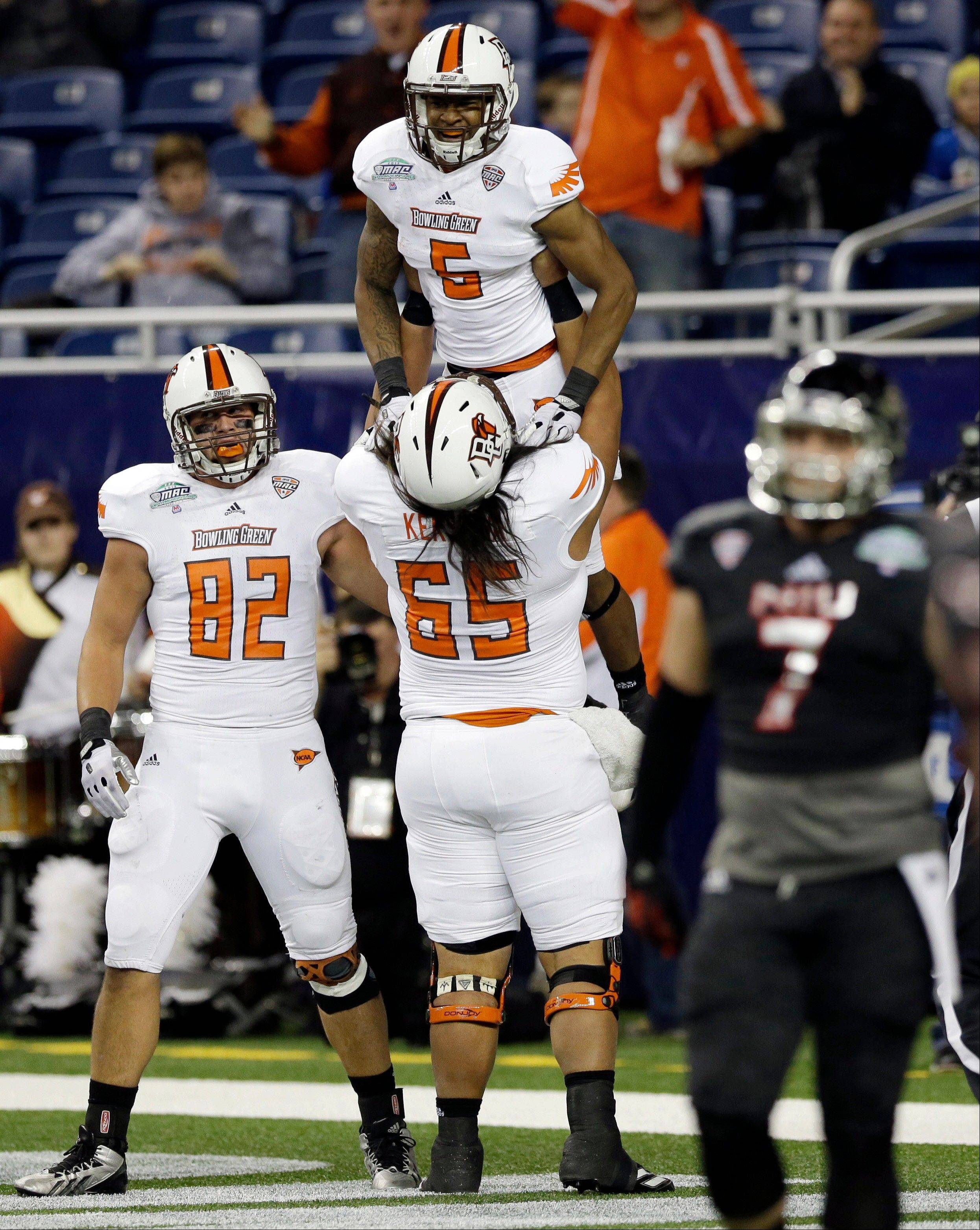Bowling Green offensive lineman David Kekuewa lifts wide receiver Ronnie Moore after Moore scored during the first half Friday against NIU.