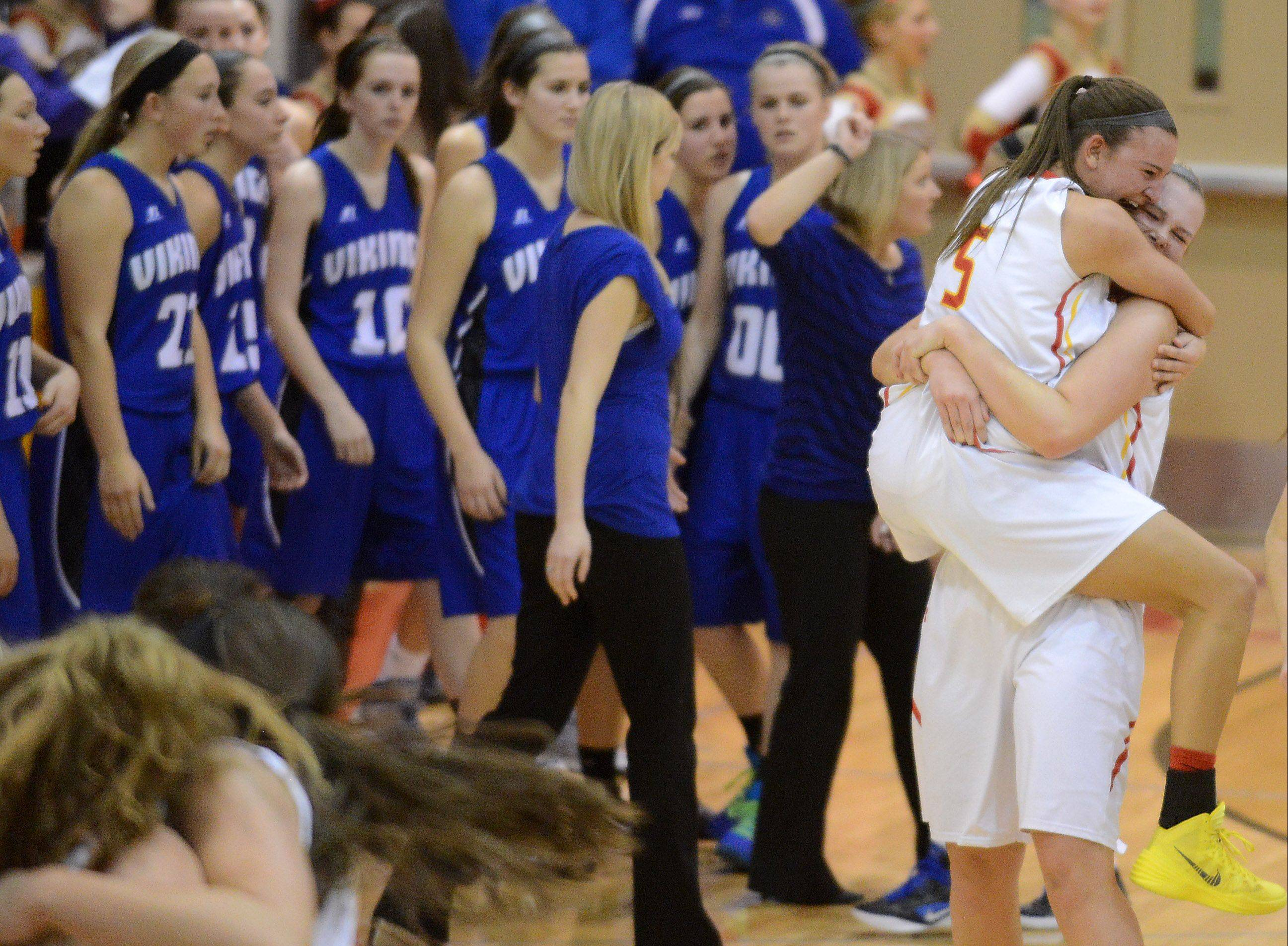 Batavia's Liza Fruendt (5) jumps in to the arms of teammate Erin Bayram (33) after beating Geneva Friday in Batavia.