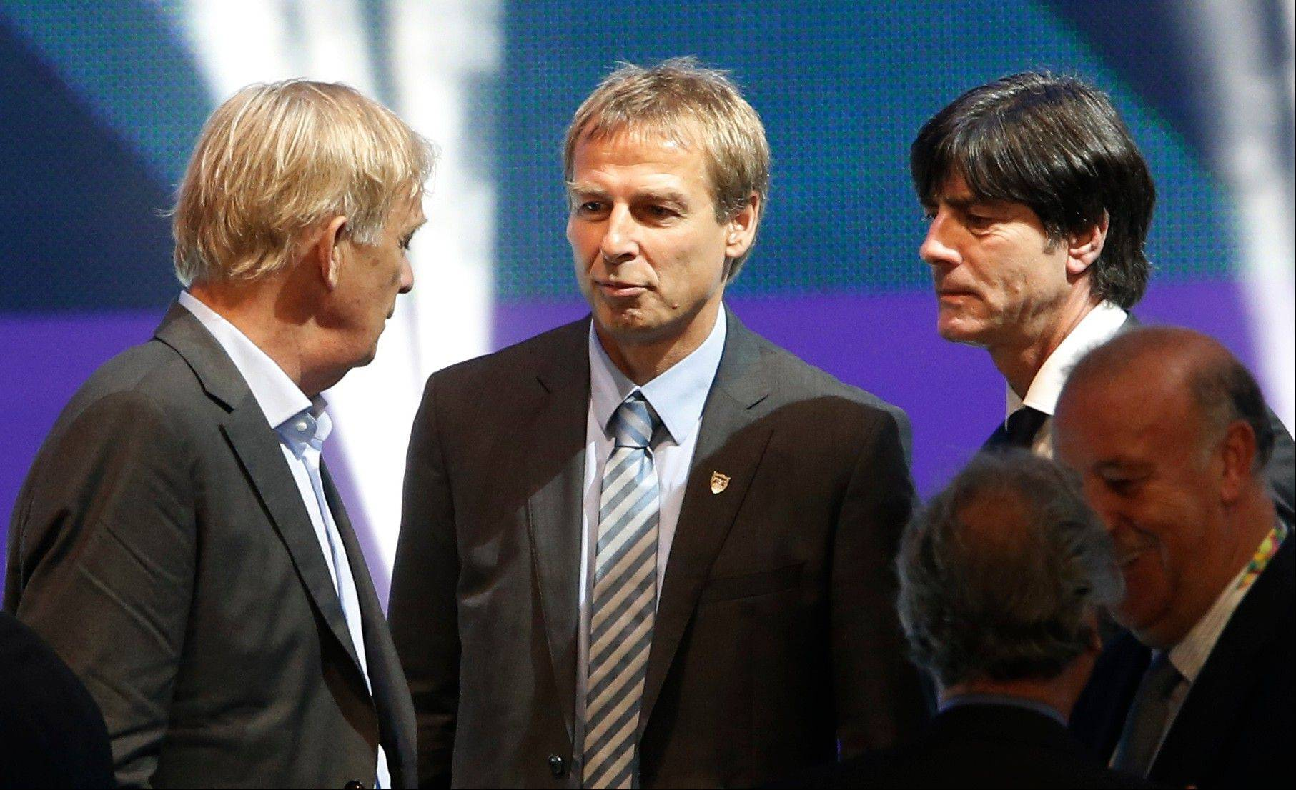 From left: Cameroon head coach Volker Finke of Germany, United States head coach Juergen Klinsmann of Germany, and Germany head coach Joachim Loew chat after the draw ceremony for the 2014 soccer World Cup.
