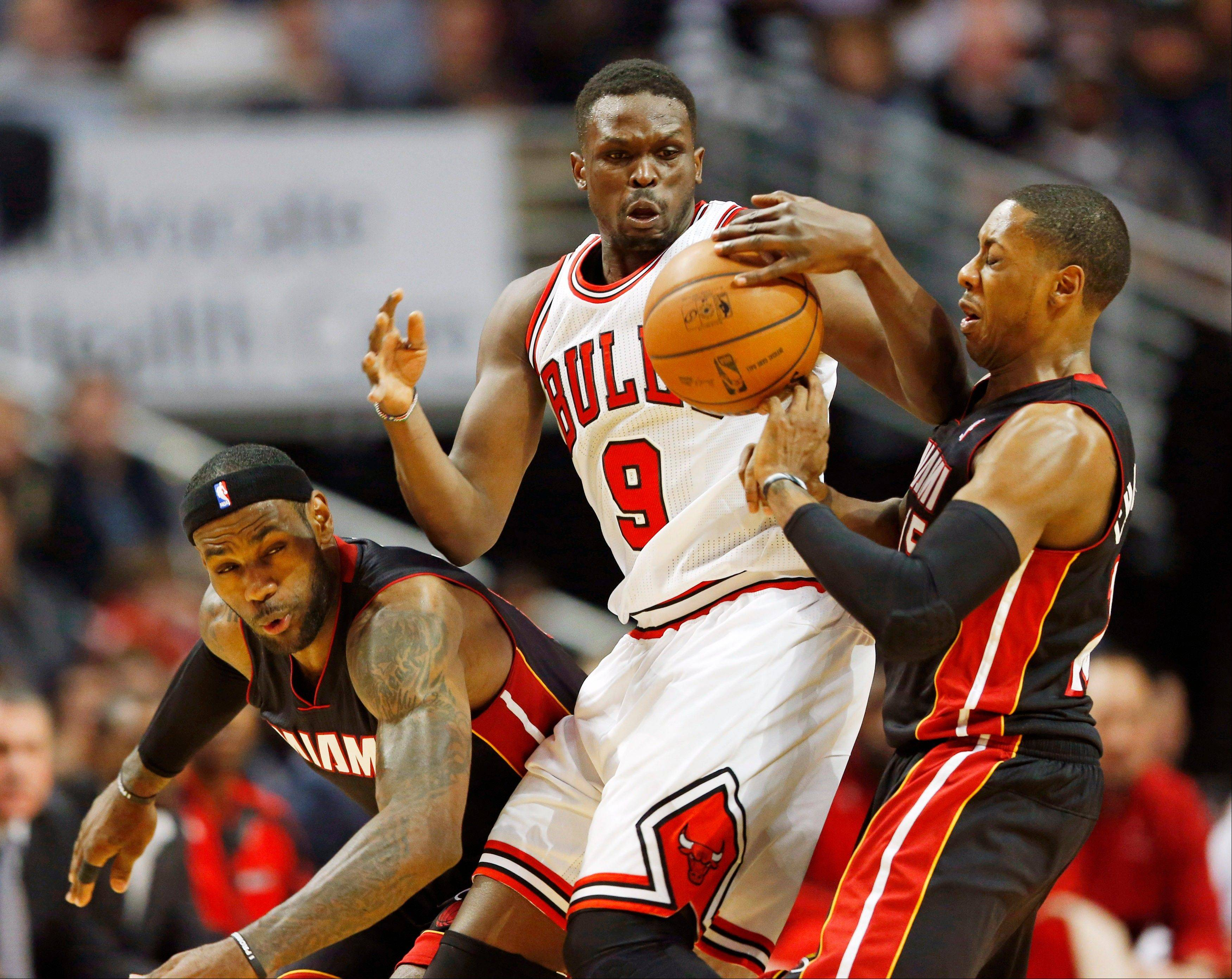 The Bulls� Luol Deng runs into traffic from the Heat�s LeBron James and Mario Chalmers on Thursday at the United Center.