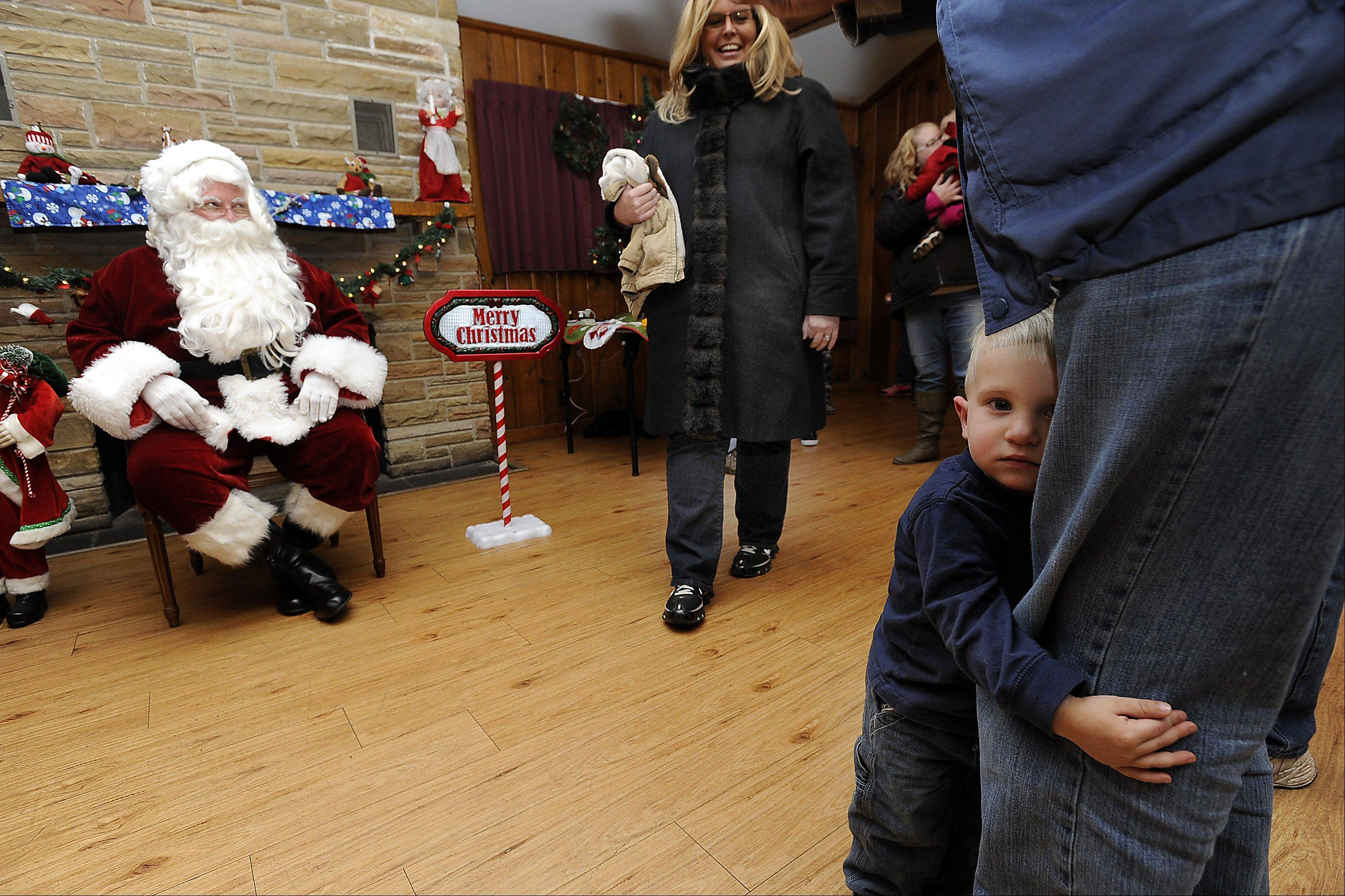 Austin McPherson, 1, of Bartlett clings to his dad Phil's leg as he shies away from Santa during the tree-lighting ceremony Friday in Bartlett.