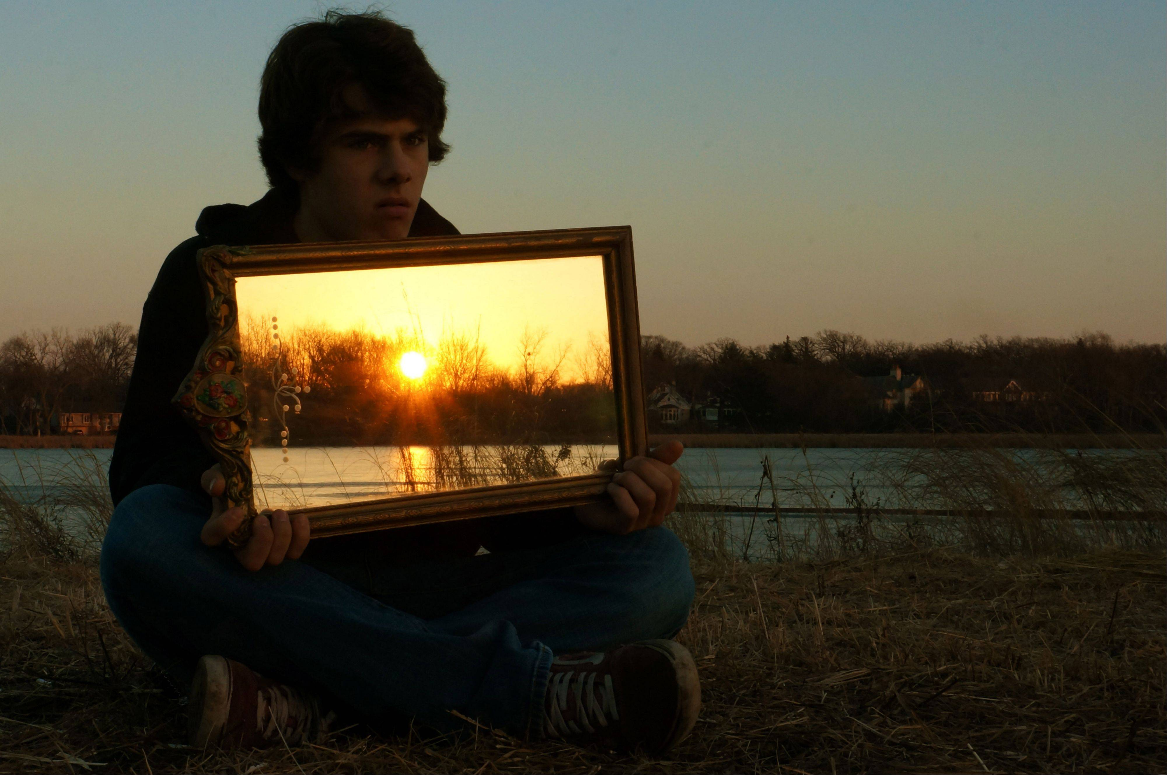 A bright orange sunset is reflected in a mirror held by a boy at Butler Lake in Libertyville last week.