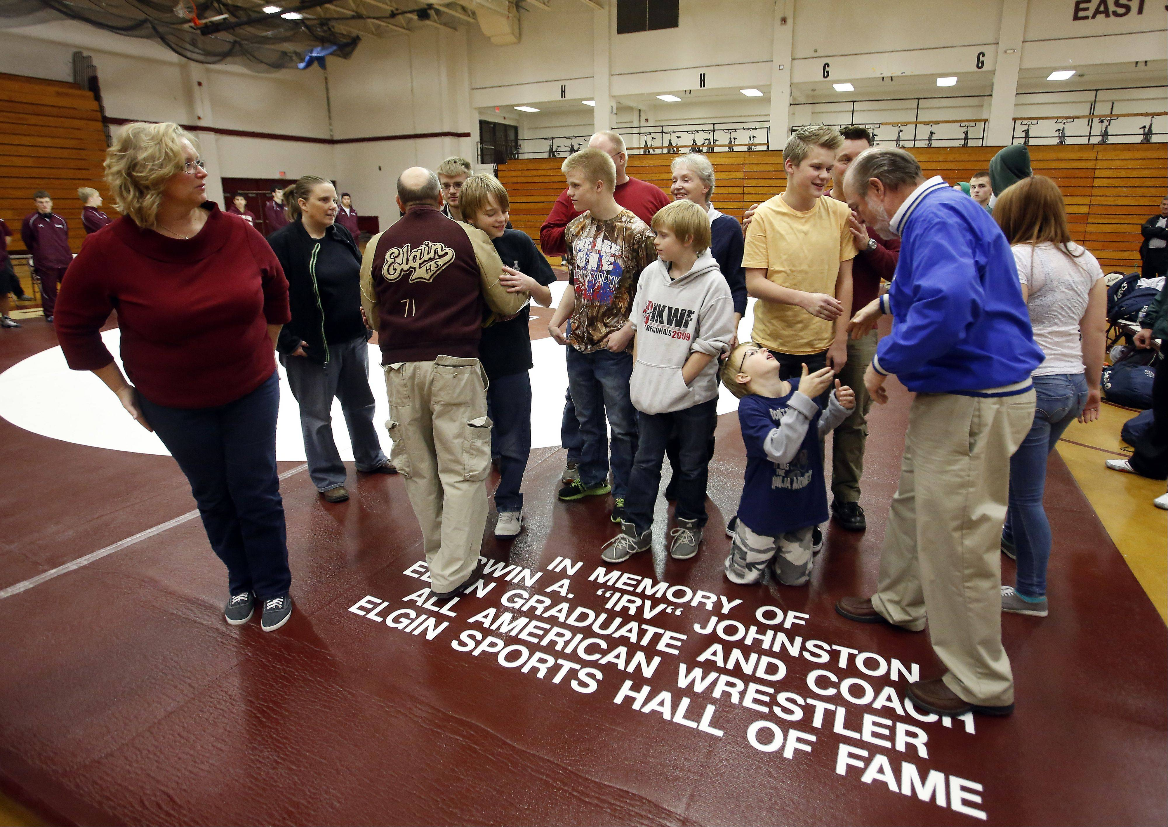 Family and friends of past coach Irv Johnston gather for a picture on the newly dedicated mat during the 10th anniversary Remembrance match Friday at Elgin High School against Bartlett.