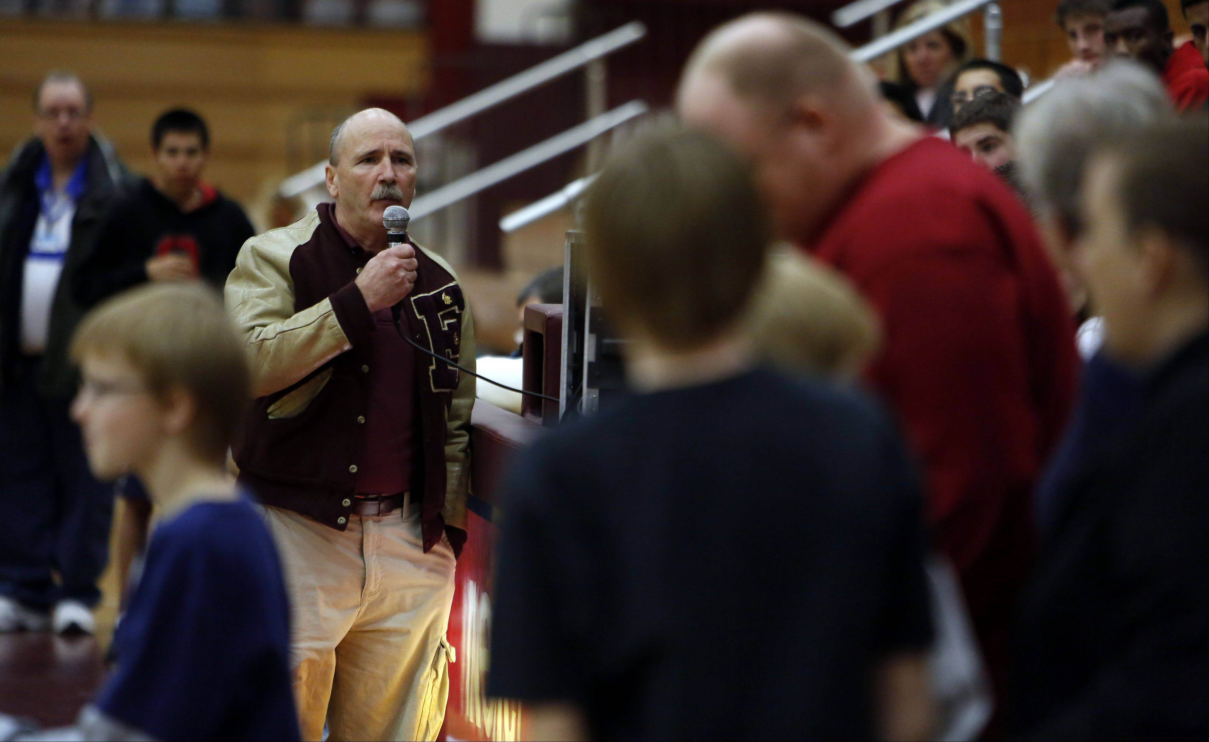 Elgin wrestling coach Tom Stewart brings some of the friends and family of past coach Irv Johnston onto the new mat during the 10th anniversary Remembrance match Friday at Elgin High School against Bartlett.