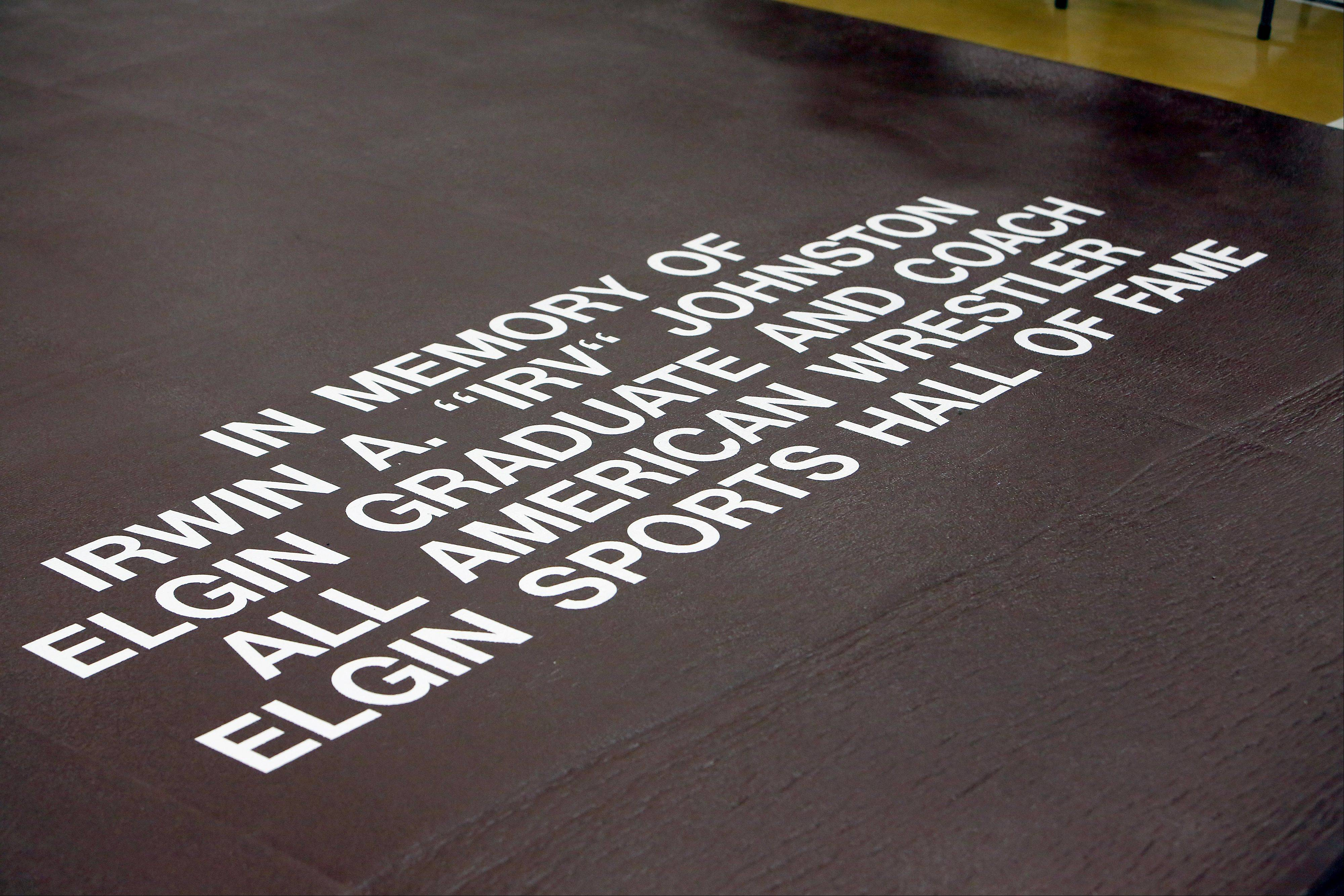The first new wrestling mat in 18 years at Elgin High School was dedicated to past coach Irv Johnston during the 10th anniversary Remembrance match Friday at Elgin High School against Bartlett.