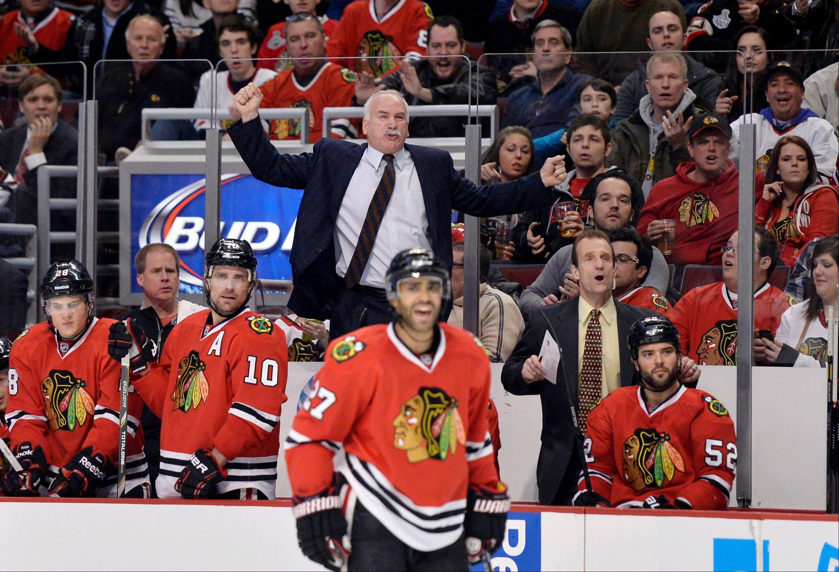 Hawks coach Joel Quenneville, center, raises his arms after the referee stopped play on a delayed penalty during the second period against the Ducks on Friday night at the United Center.