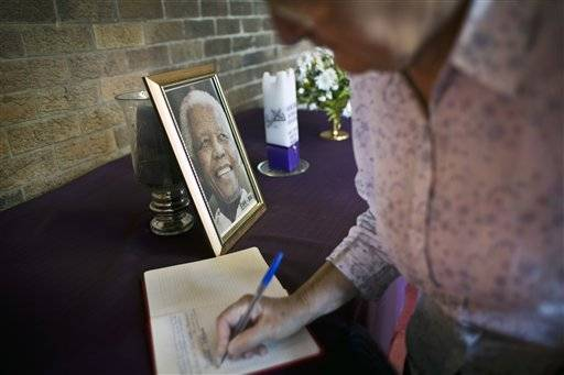 A mourner signs the book of condolences at the iconic Regina Mundi church, which became one of the focal points of the anti-apartheid struggle, in Soweto, Johannesburg, South Africa Saturday, Dec. 7, 2013. South Africa is readying itself for the arrival of a flood of world leaders for the funeral and memorial services for former president Nelson Mandela as thousands of mourners continue to flock to sites around the country to pay homage to the freedom struggle icon.