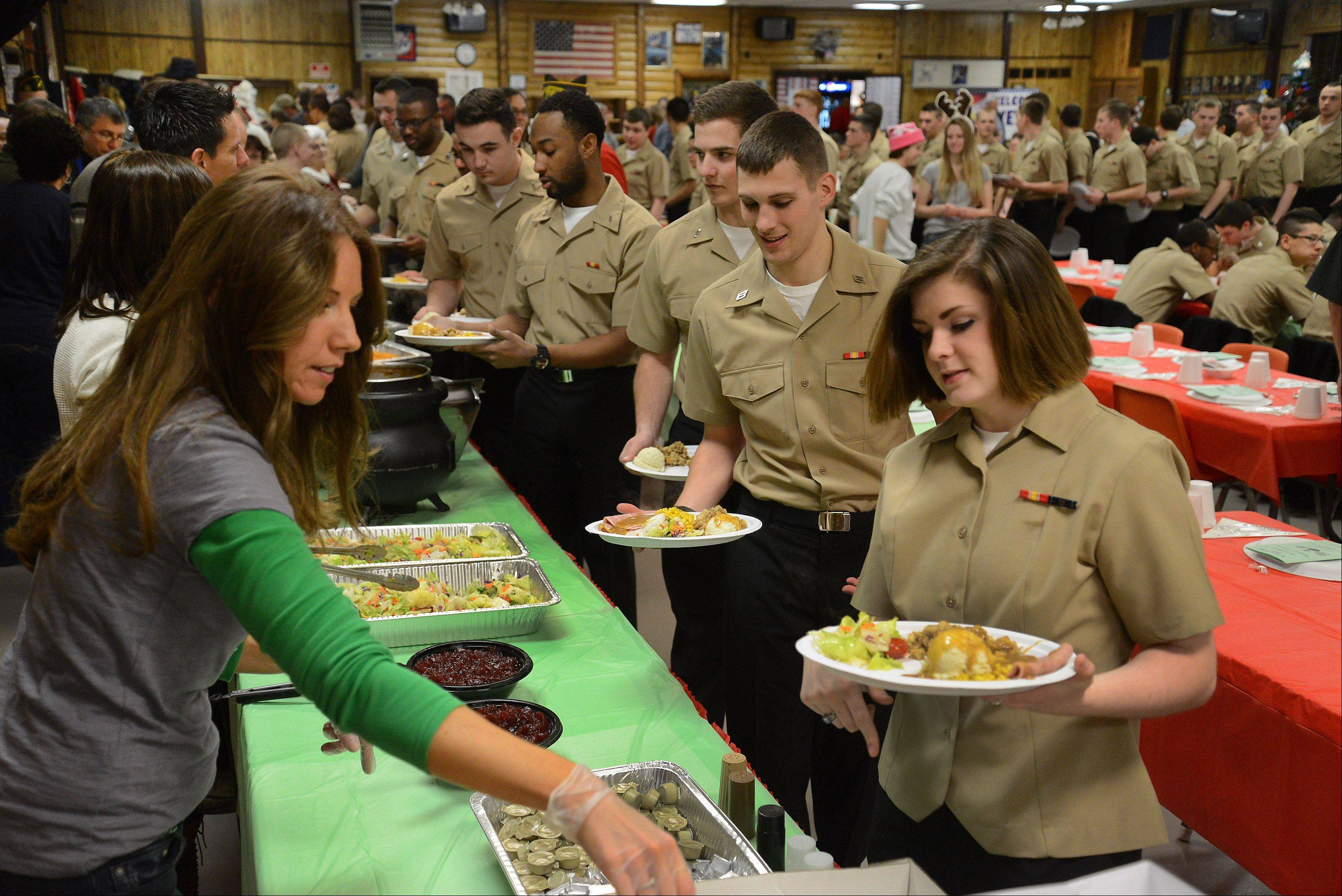 First time volunteer Julie Besson of Antioch, left, serves up cranberry and rolls Saturday as the VFW in Antioch hosted 350 sailors from Great Lakes and 50 veterans from Lovell and Hines hospitals for a full Christmas dinner .