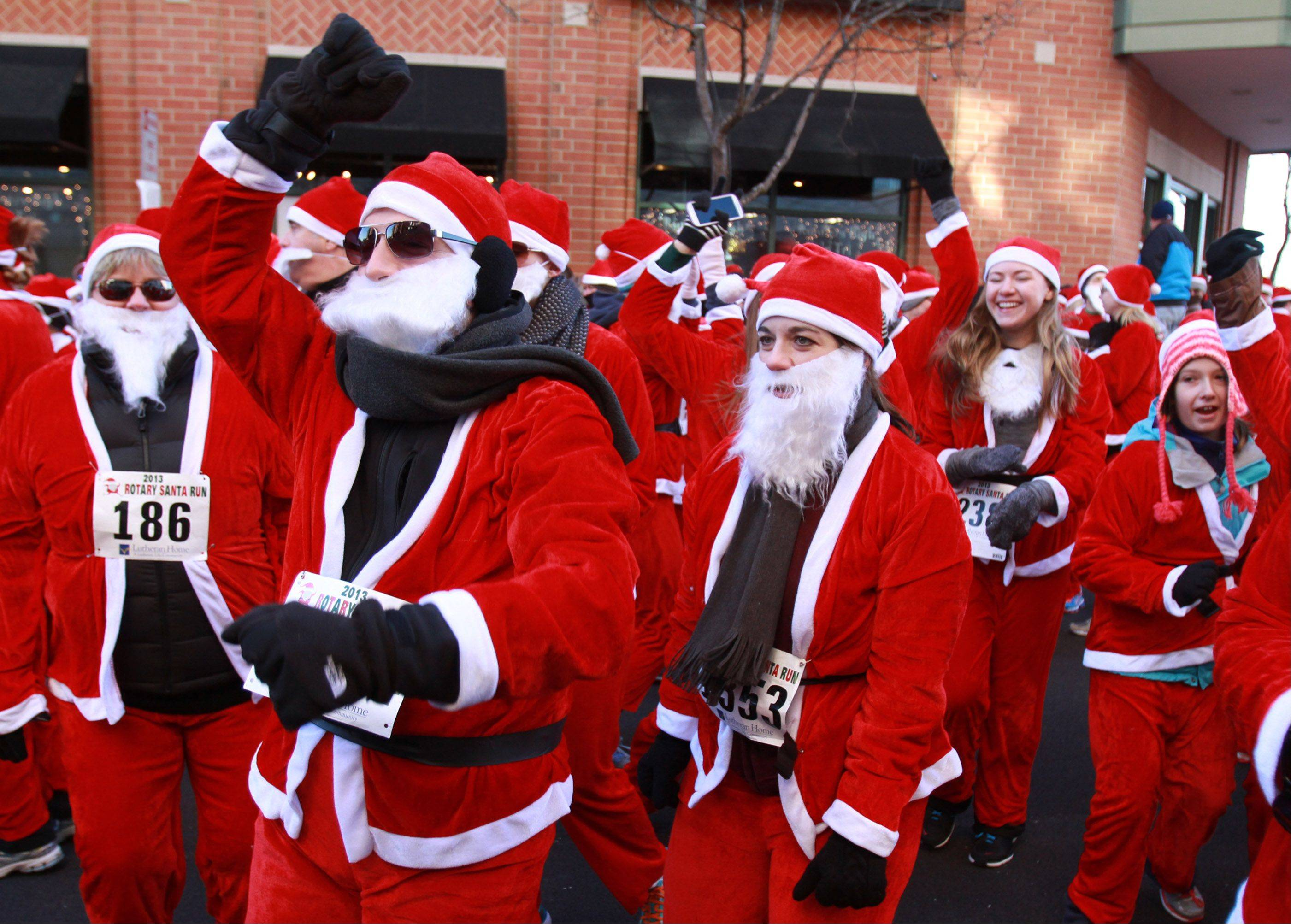 Jeff Zilke, a Palatine resident and a teacher at Sundling Junior High, warms up by dancing before the Rotary Santa Run on Saturday in Arlington Heights.