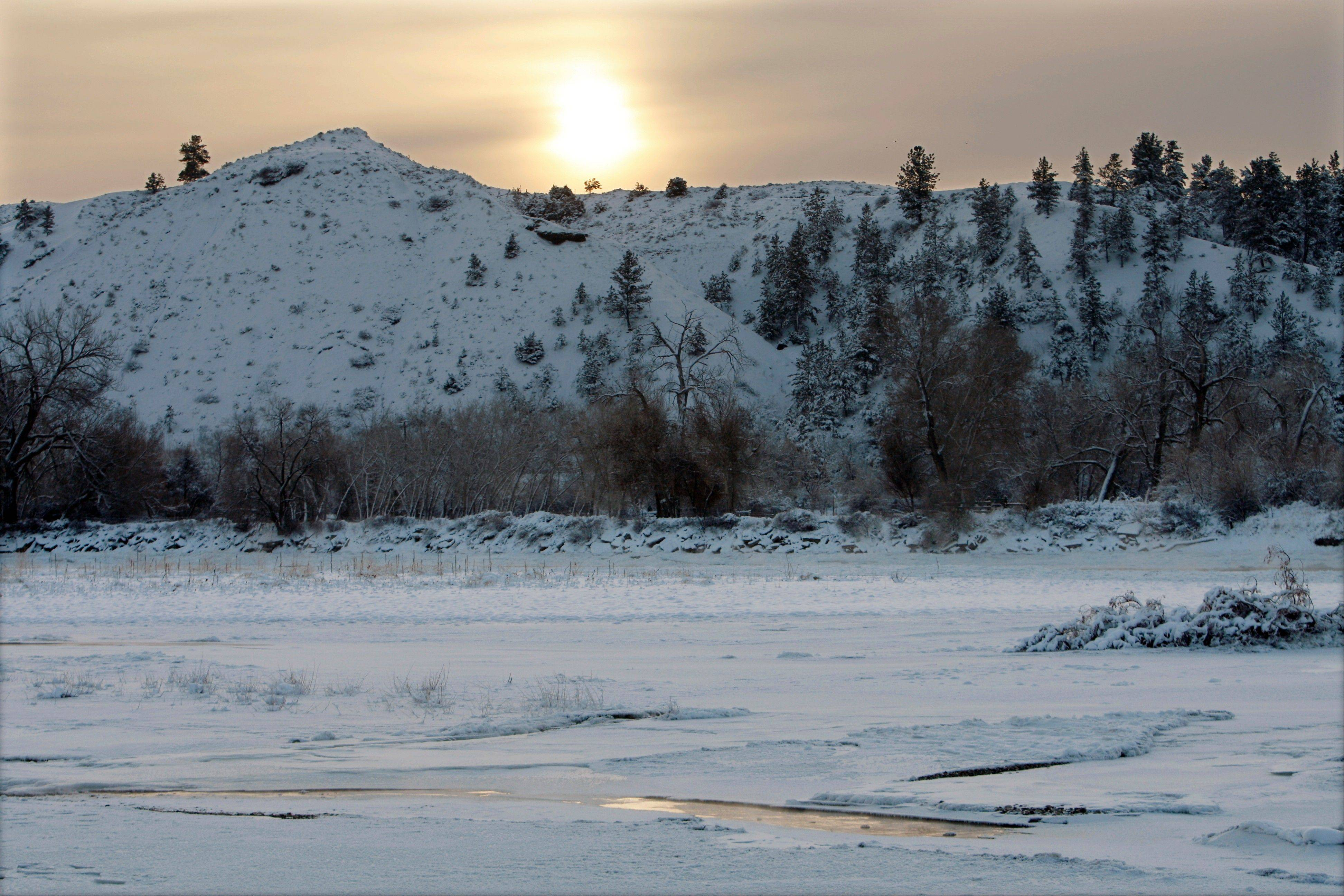 The sun rises Saturday over the hills south of the Yellowstone River in Billings, Mont. as the temperatures hover around 20 degrees below zero.