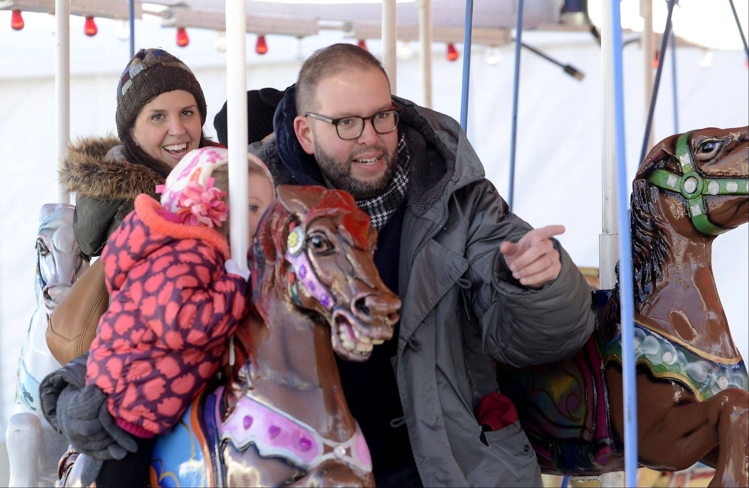 Anne and Ethan Baumfeld of Barrington and their children, Harper and Perry, ride the merry-go-round Saturday at ChristKindlFest in downtown Barrington.