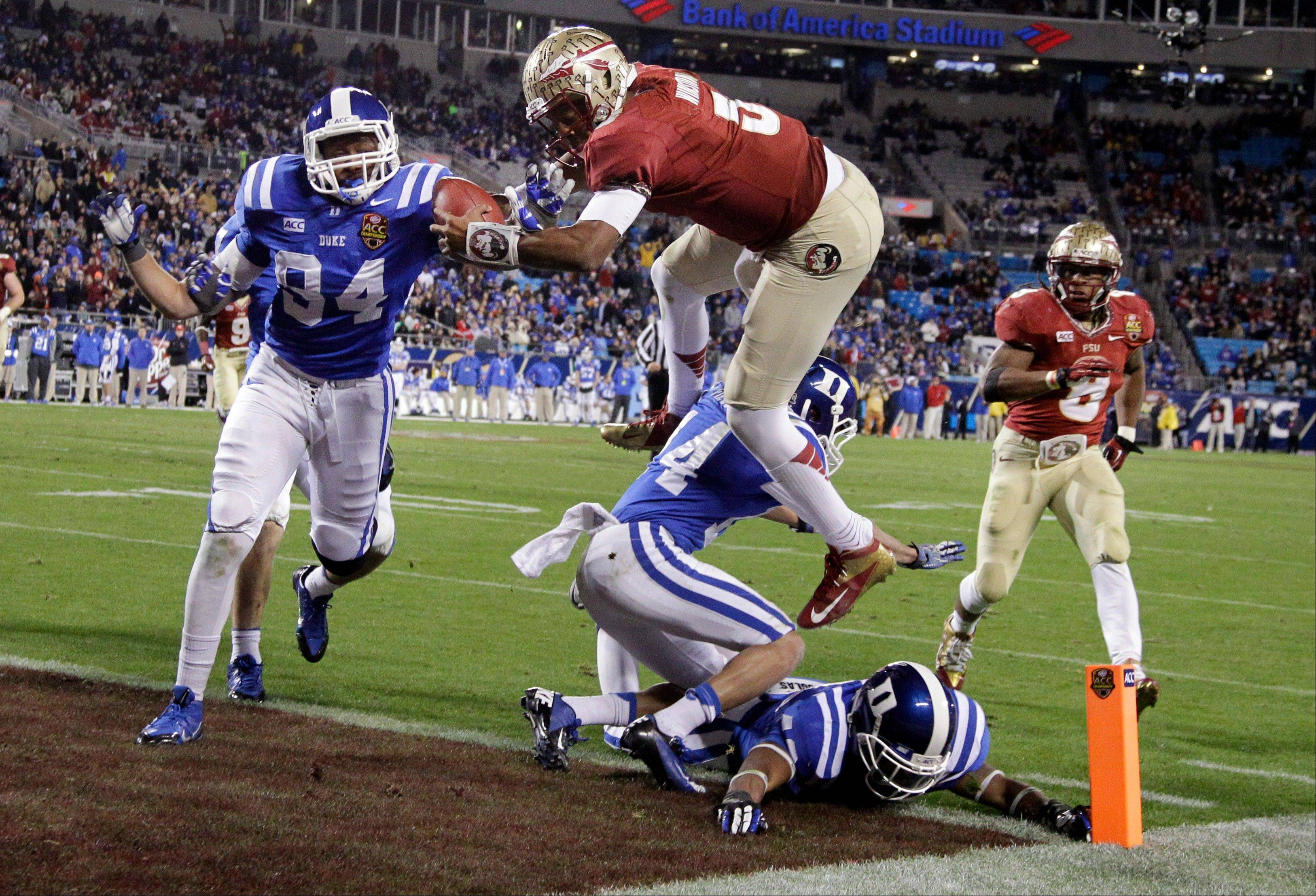 Florida State�s Jameis Winston (5) leaps over Duke�s Bryon Fields (14) for a touchdown during the Atlantic Coast Conference Championship Saturday in Charlotte, N.C.